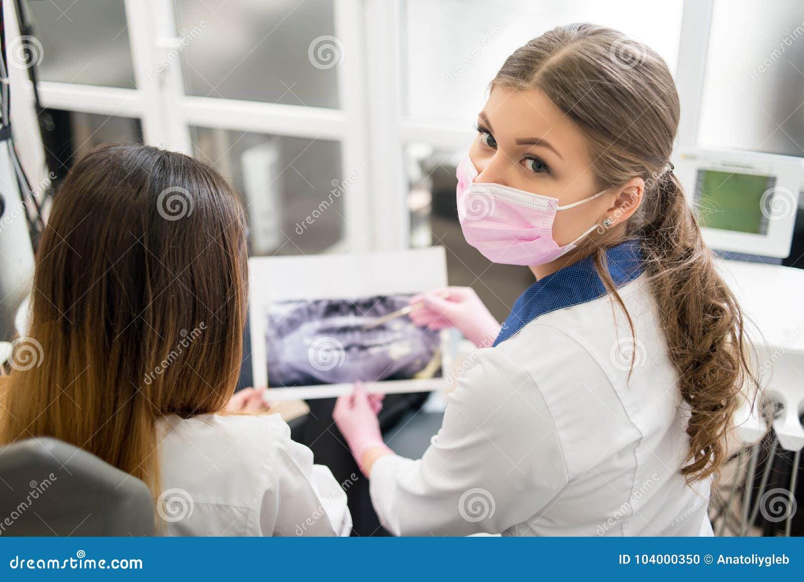 女性年轻与女性患者的牙医审查的X-射线图象在牙齿办公室,看对照相机 牙科