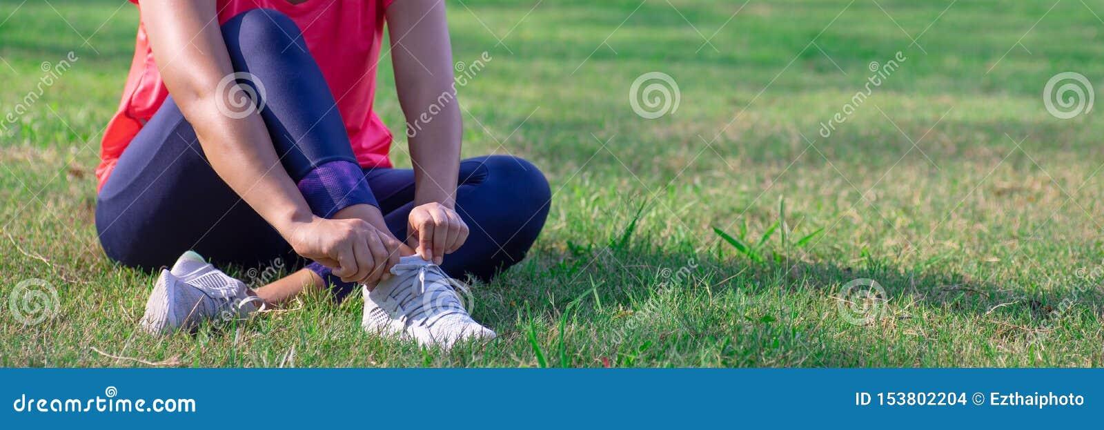 女性手在实践前调整她的跑鞋 准备好的赛跑者训练 体育活跃生活方式概念 ??
