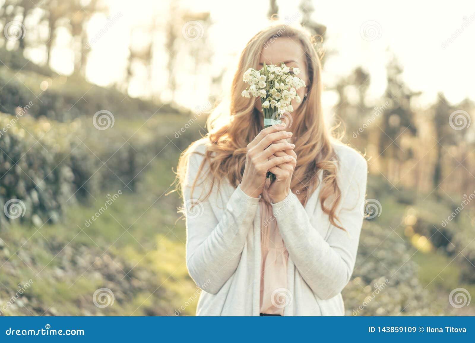 女性手拿着snowdrops特写镜头花束
