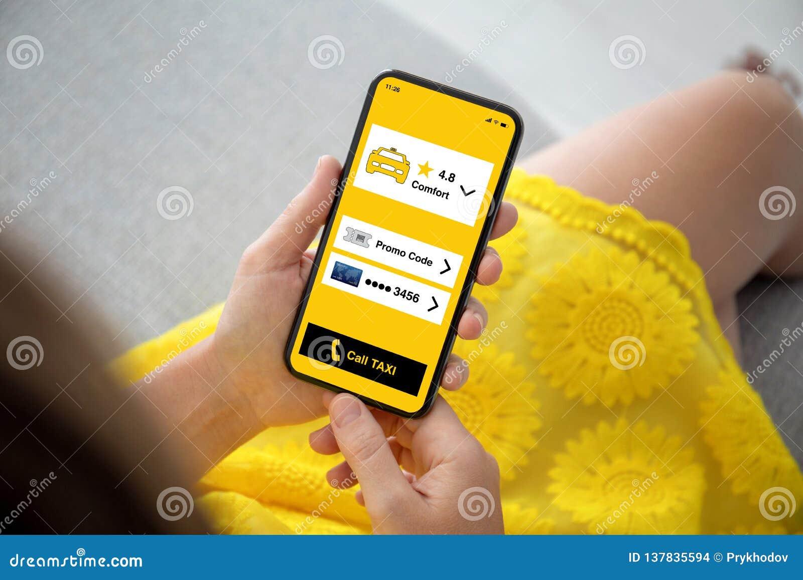 女性手染黄礼服有应用程序电话出租汽车的藏品电话