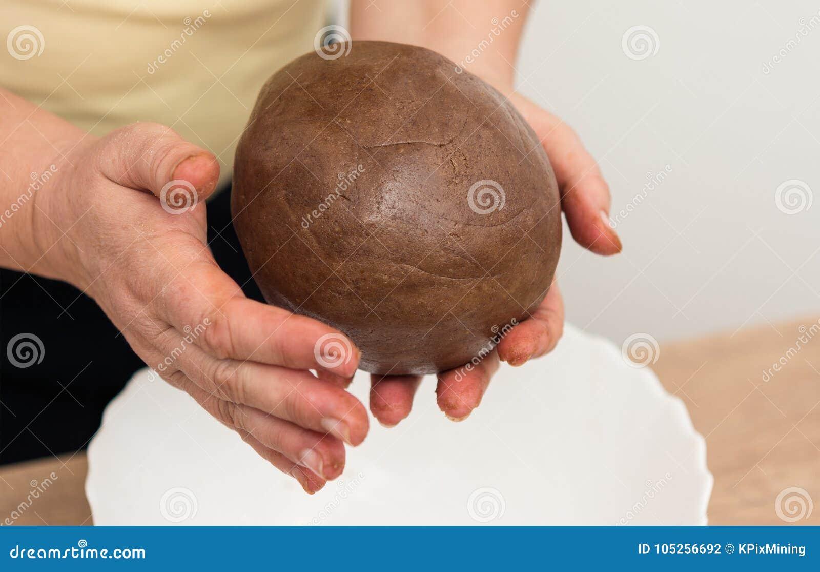 女性手特写镜头,当揉棕色面团时球
