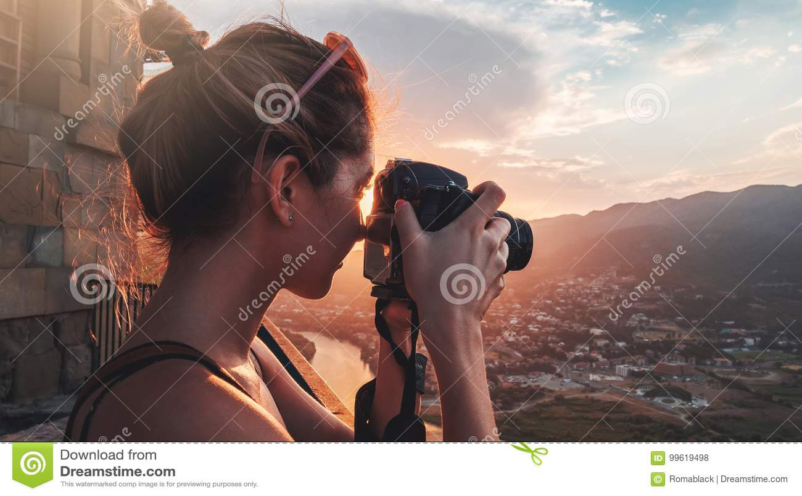 女性摄影师,为山风景照相在日落