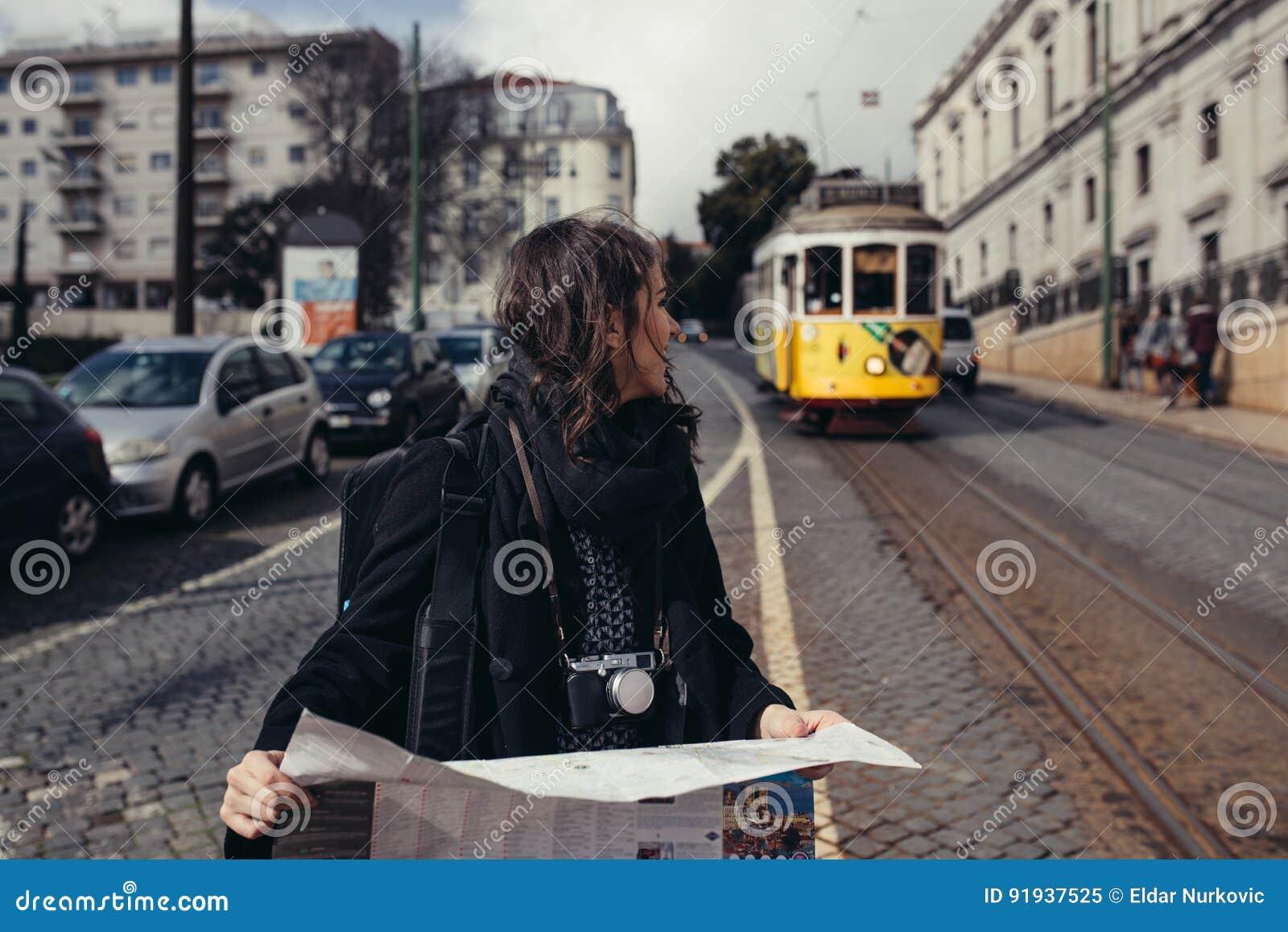 女性旅客藏品和读书游人地图