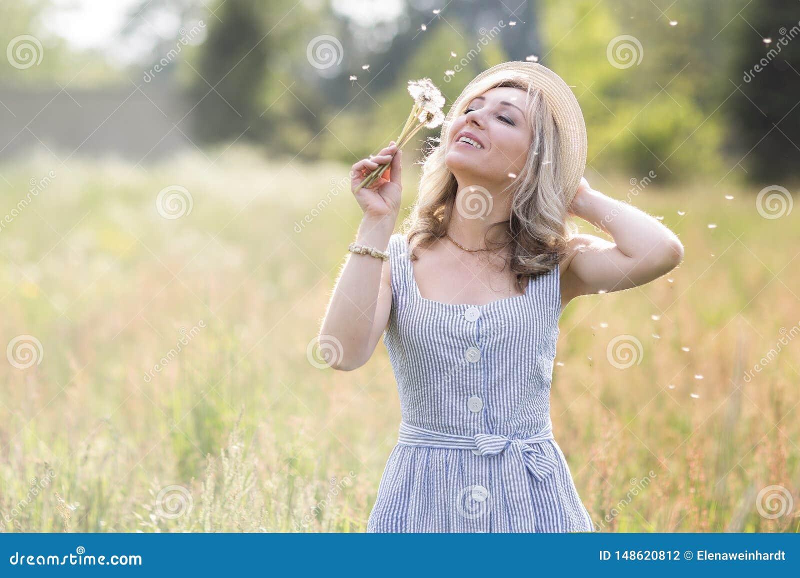 女性画象户外 一个草帽的一名妇女在与野花花束的一块花田