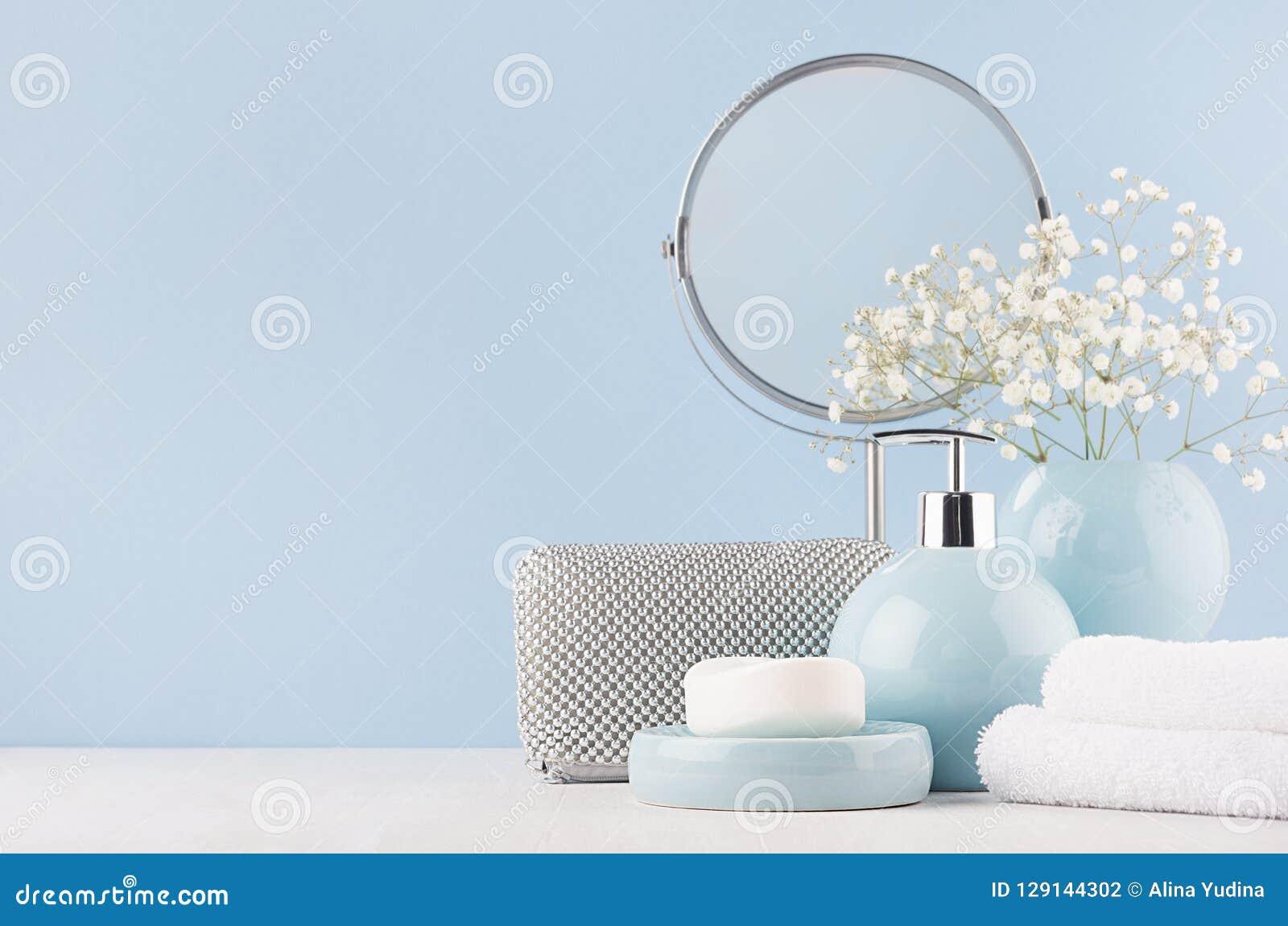女性的卫生间装饰轻的软的蓝色颜色的-盘旋镜子、银色化妆袋子、白花、毛巾、肥皂和花瓶