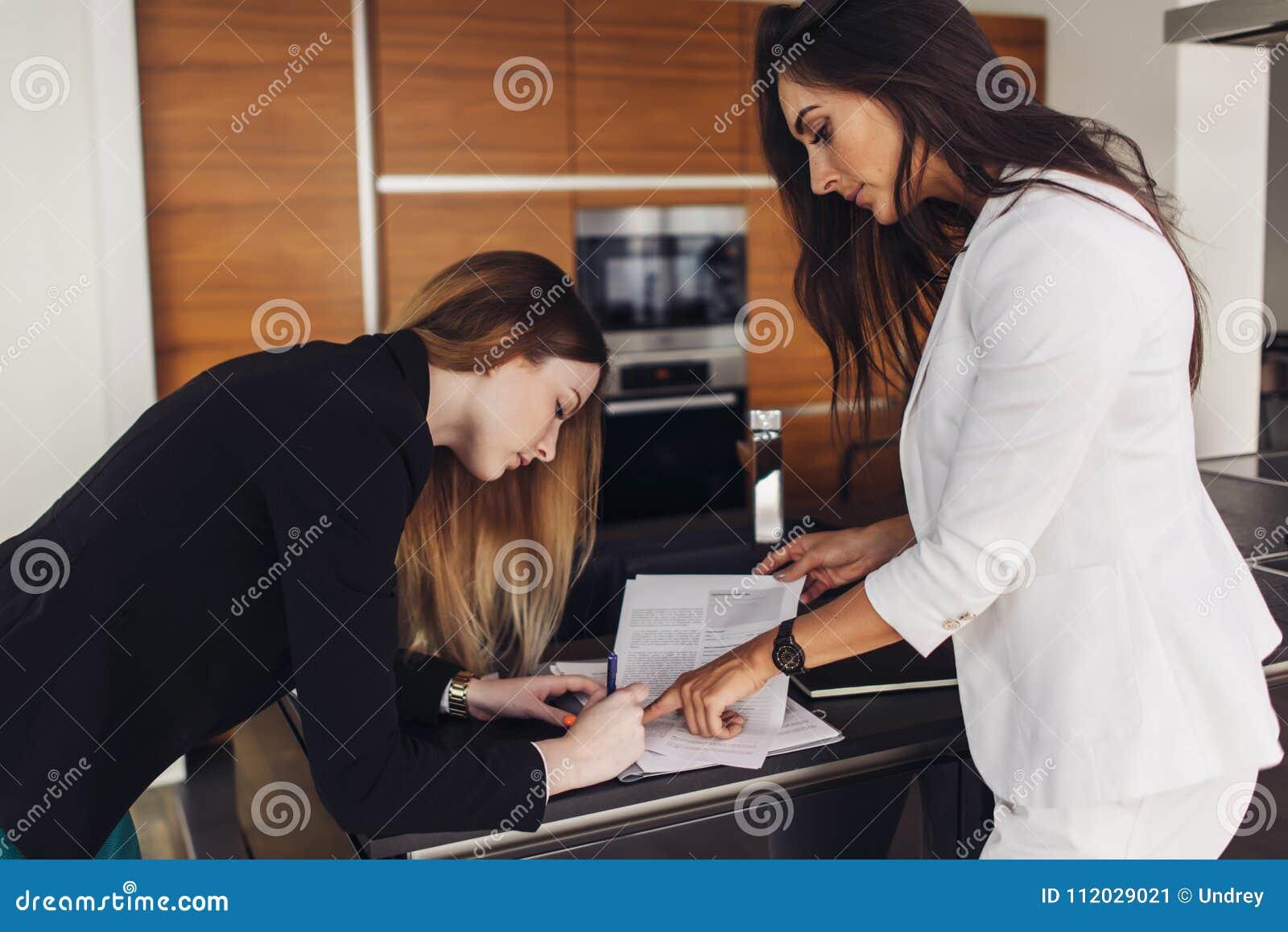 女性签署住宅销售合同和购买的地产商和顾客站立在新的公寓厨房里