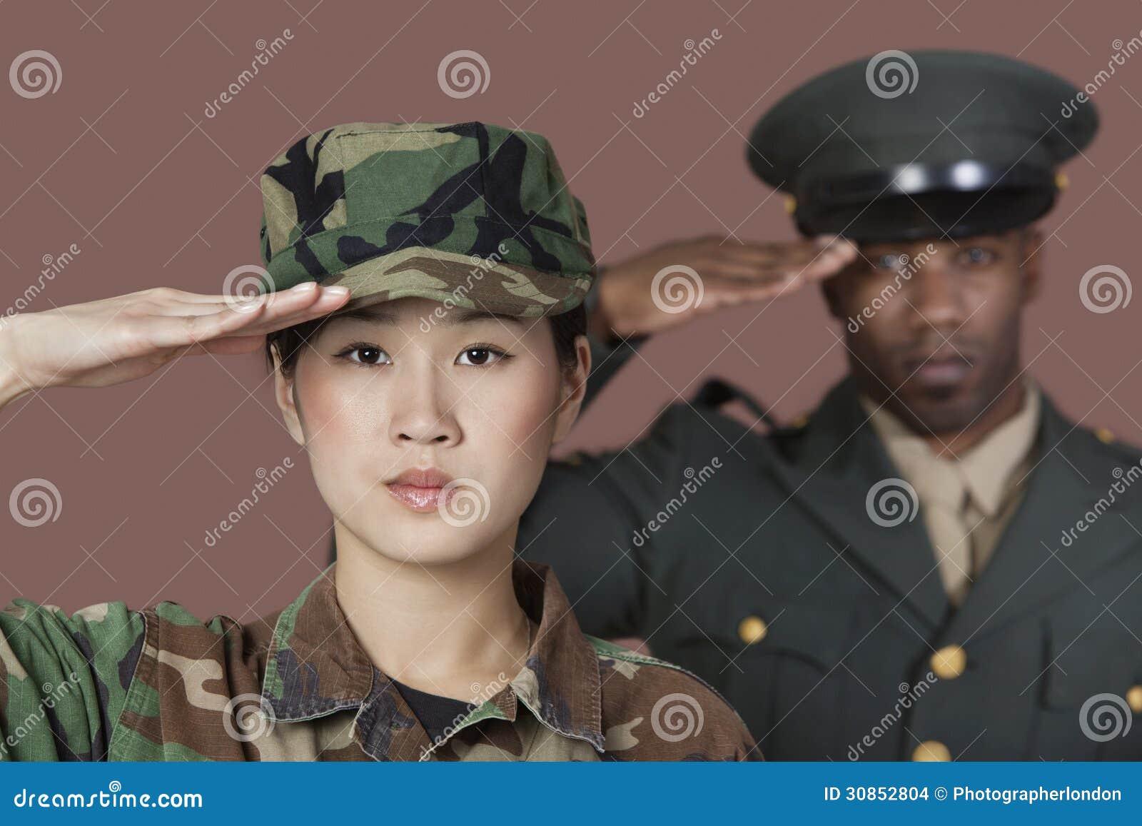 年轻女性美国陆战队战士特写镜头画象有向致敬在棕色背景的男性官员的