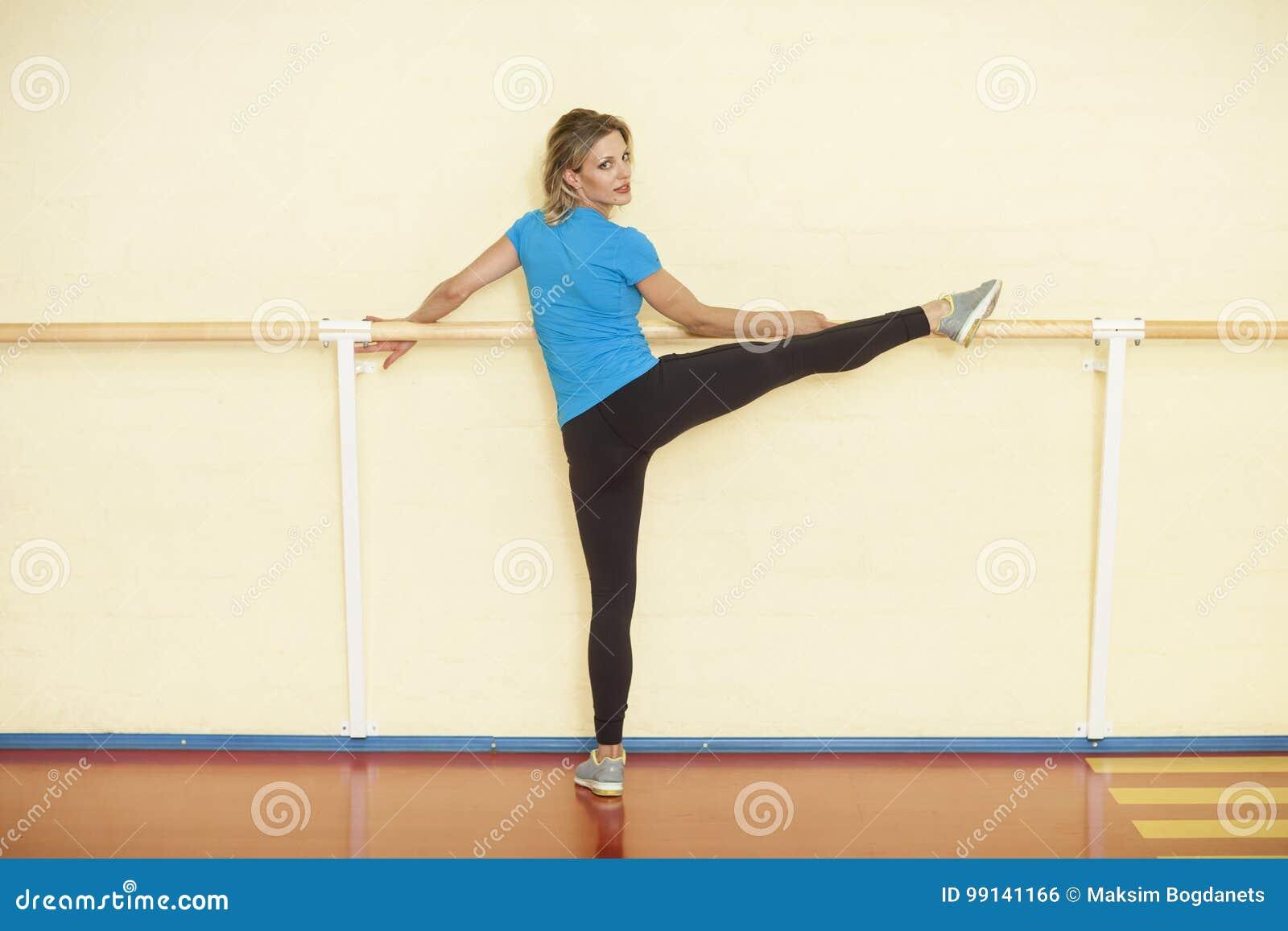 女性舒展在与扶手栏杆的五颜六色的健身类