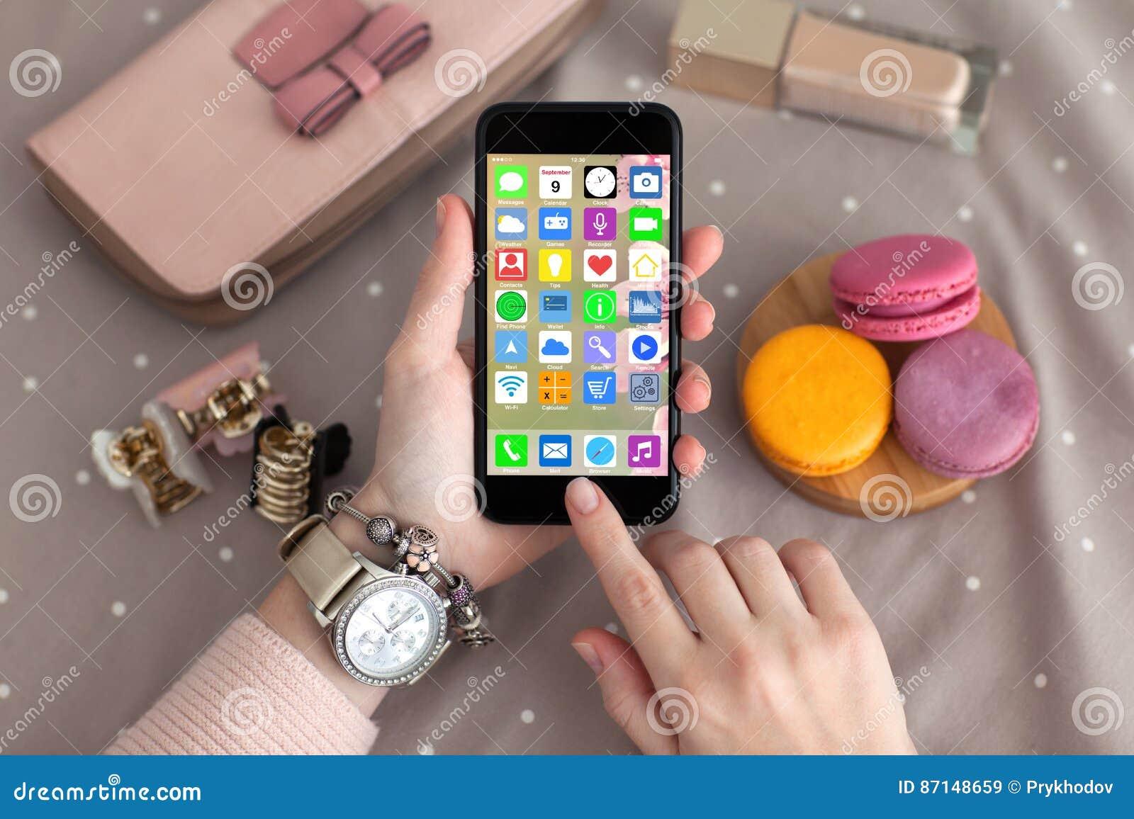 女性递拿着有家庭屏幕象apps的首饰电话