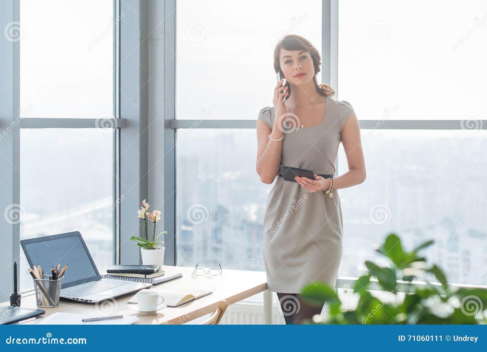 年轻女性顾问有企业电话在办公室在她的工作场所 秘书说在巧妙的电话里,举行