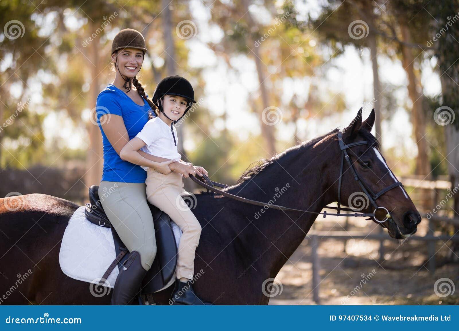 女性骑师和女孩坐的马术画象