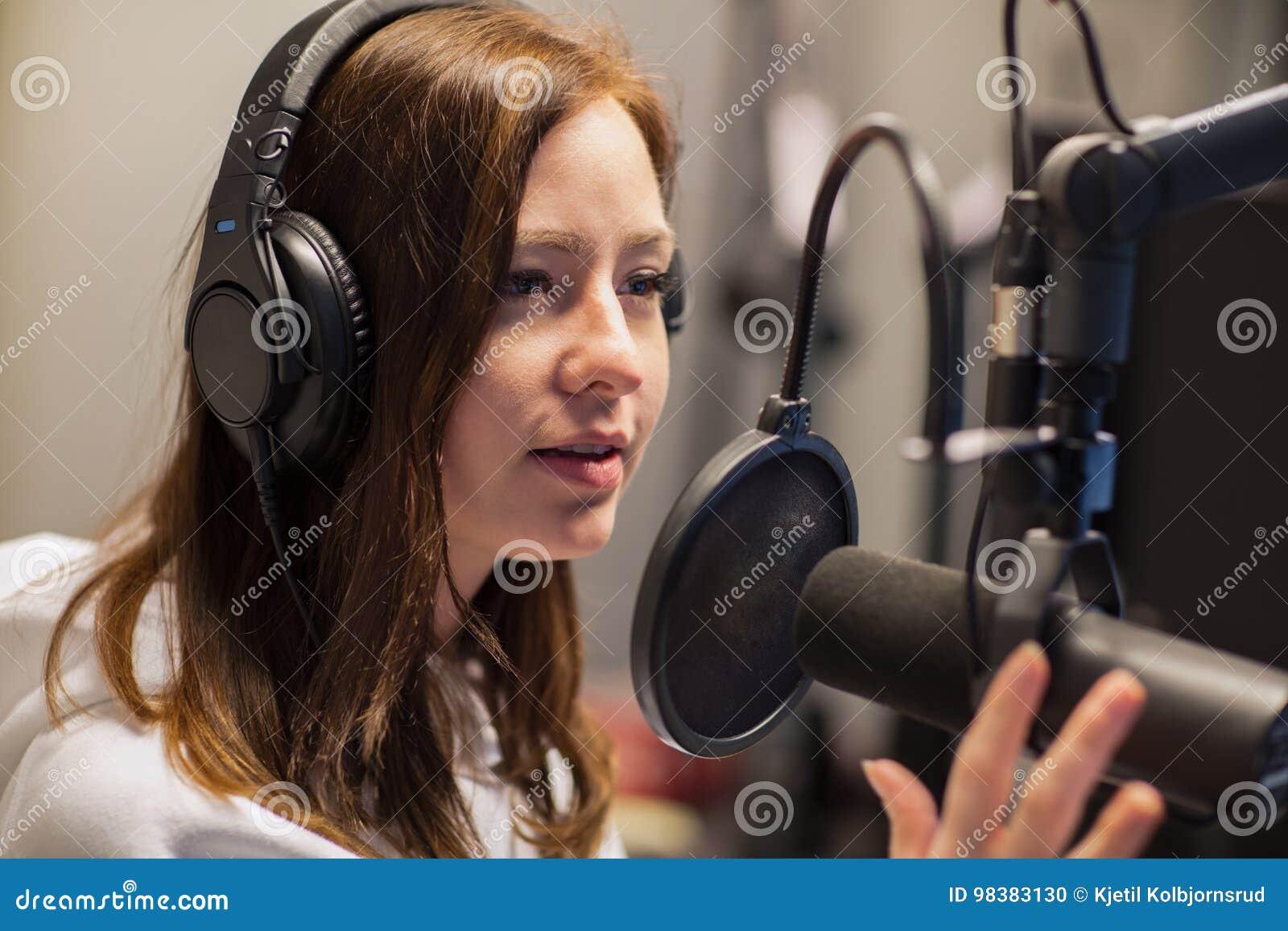 女性骑师谈话在话筒在无线电演播室