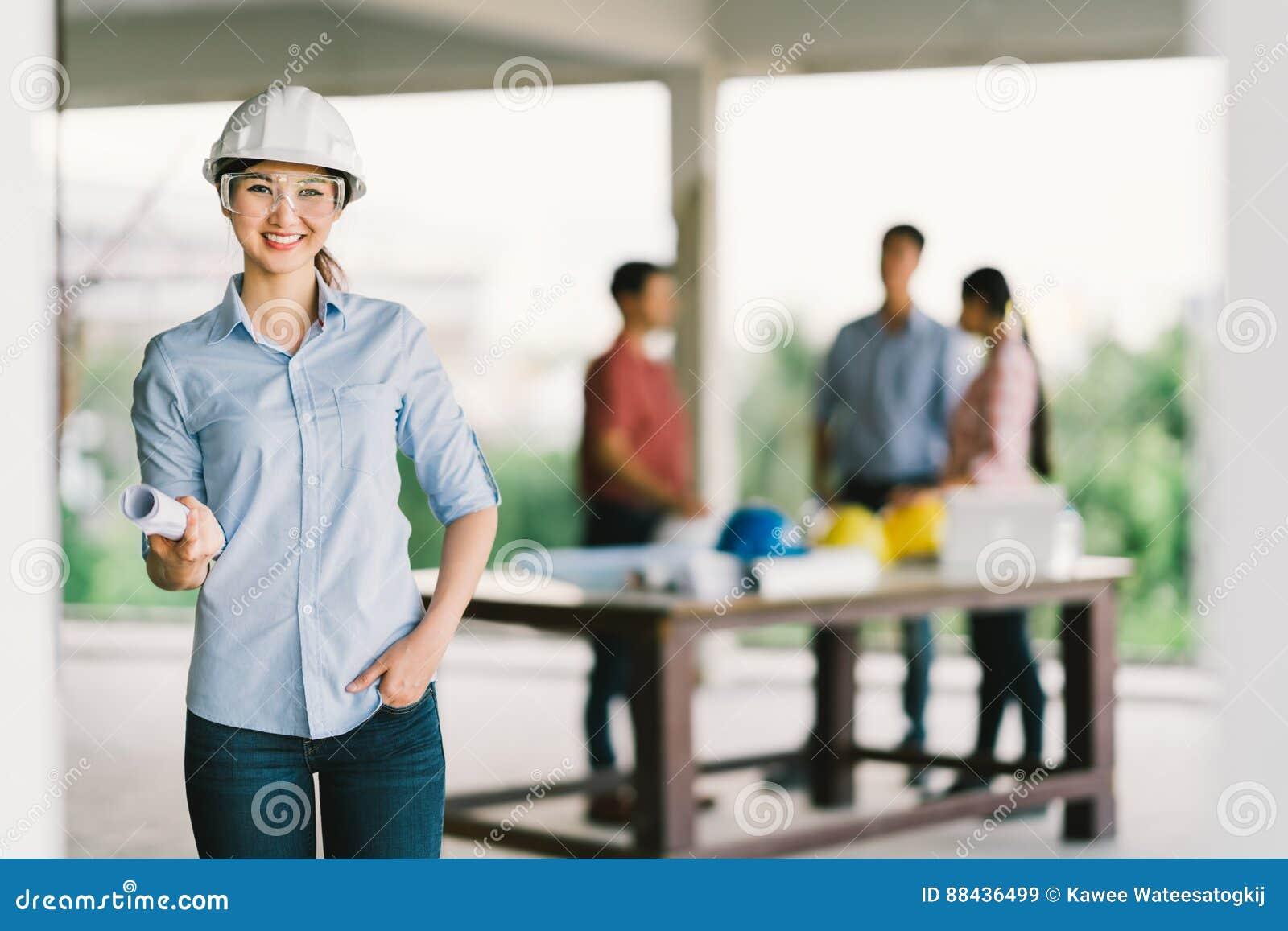 女性建筑师或工程师有图纸的在楼房建筑站点 关于迷离背景的工友会议