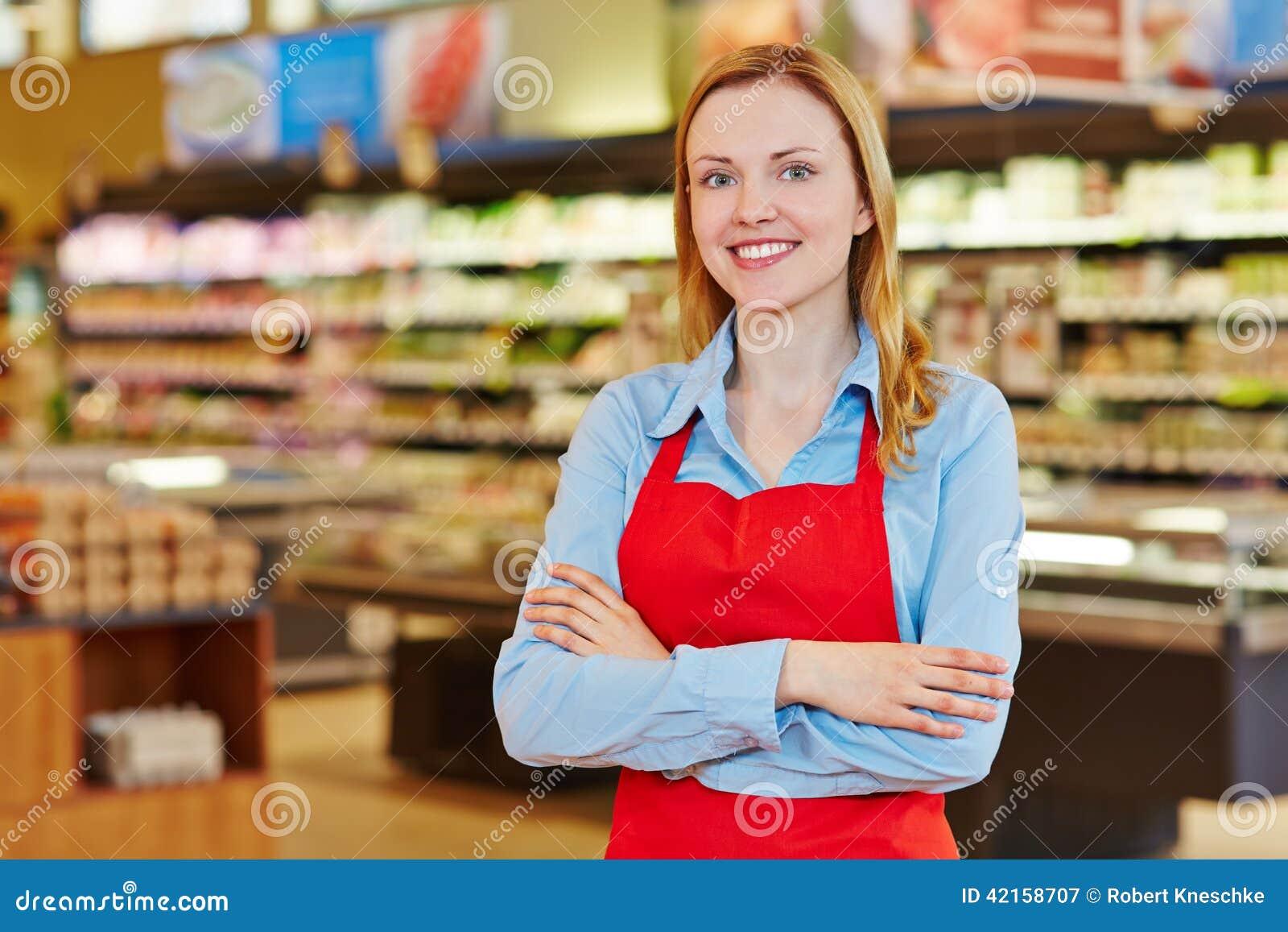 有红色围裙的年轻愉快的女推销员在超级市场.图片