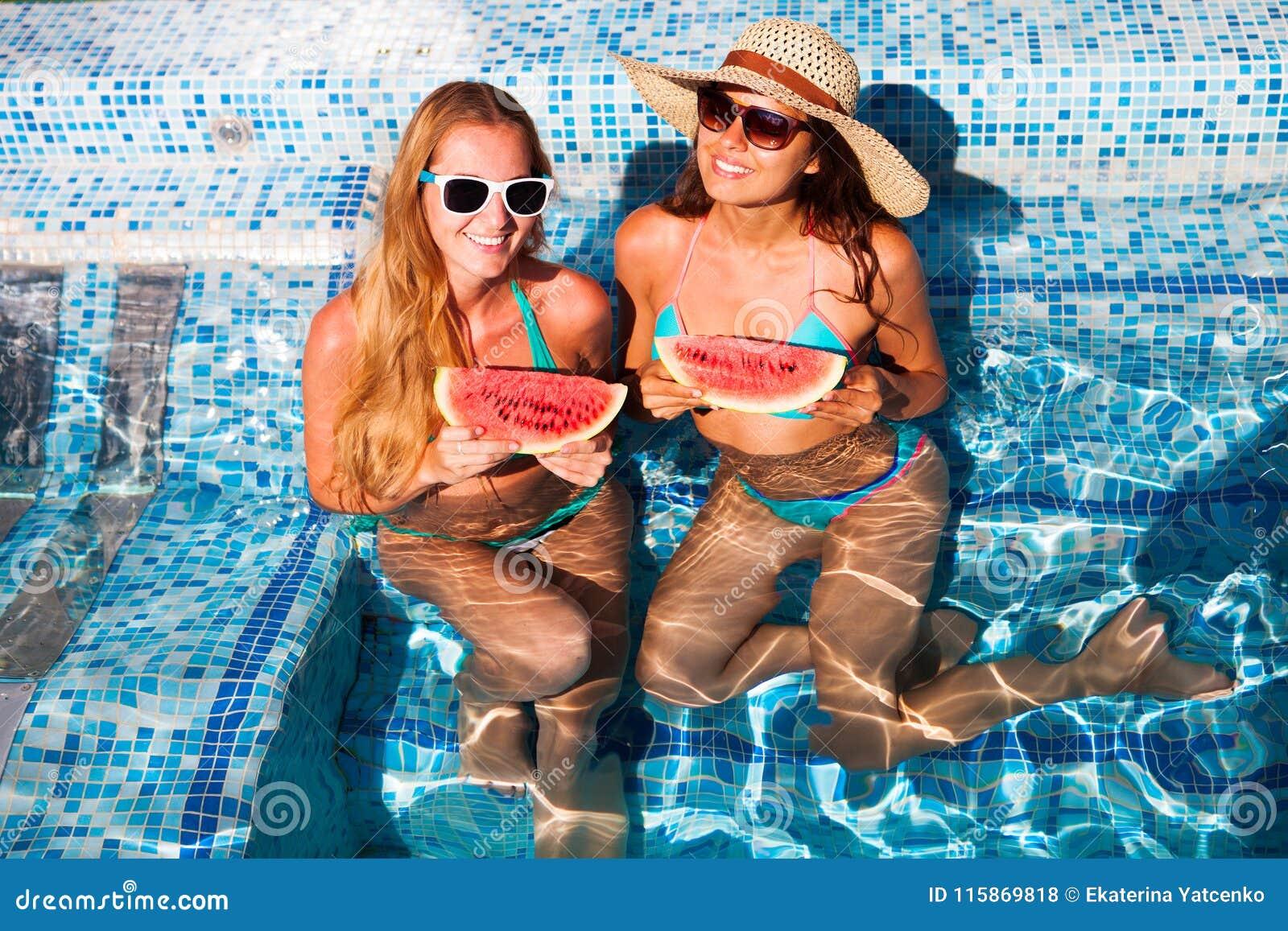 女朋友举行一半在一个蓝色水池的一个红色西瓜,放松