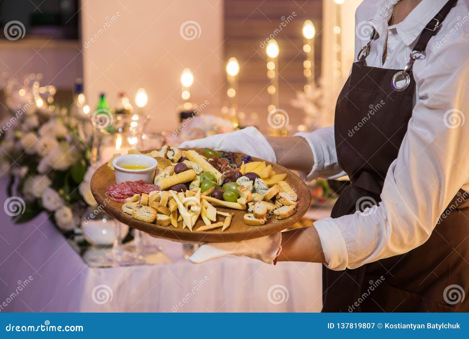 女服务员拿着一个木盘用肉和乳酪
