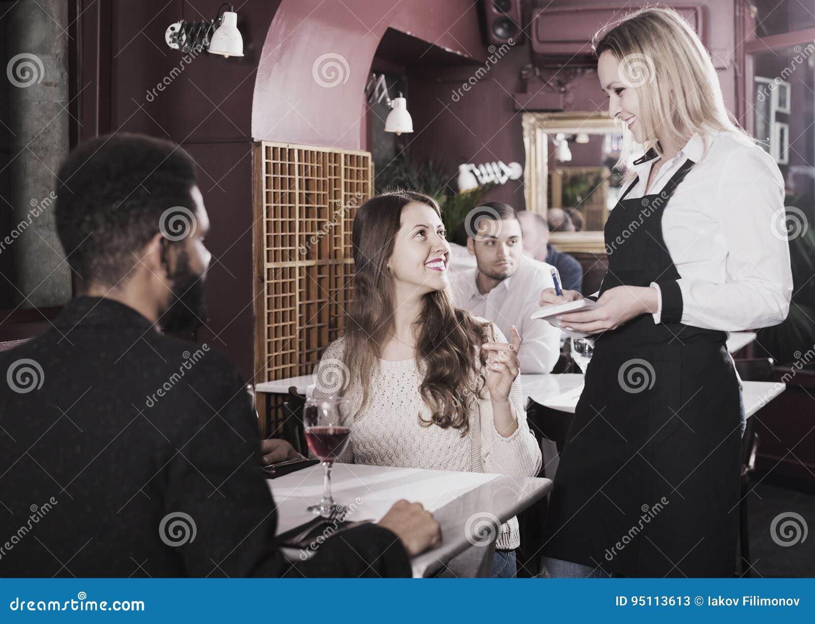 女服务员年轻夫妇的服务膳食在桌上