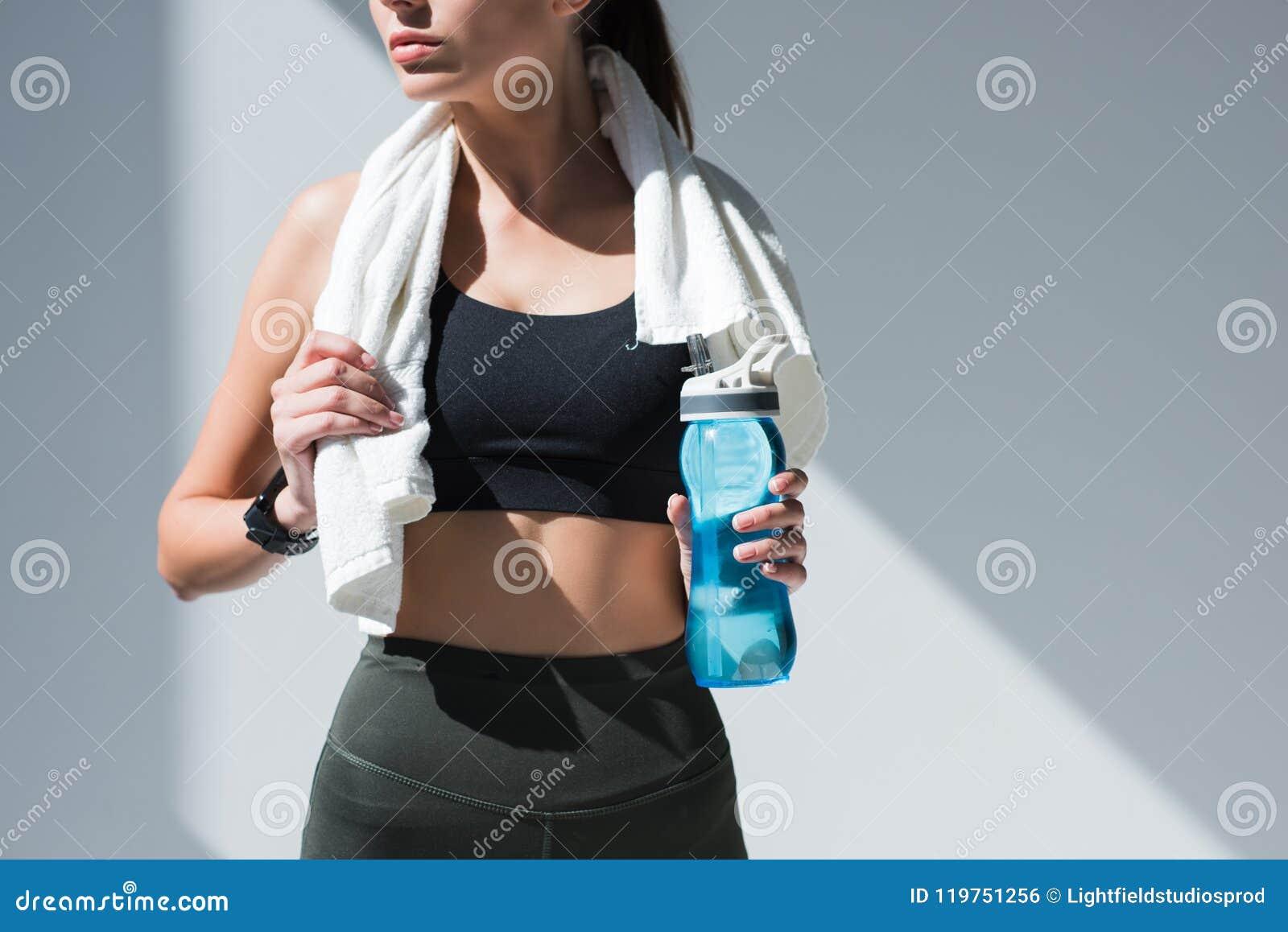 女运动员播种的射击有拿着瓶水的毛巾的