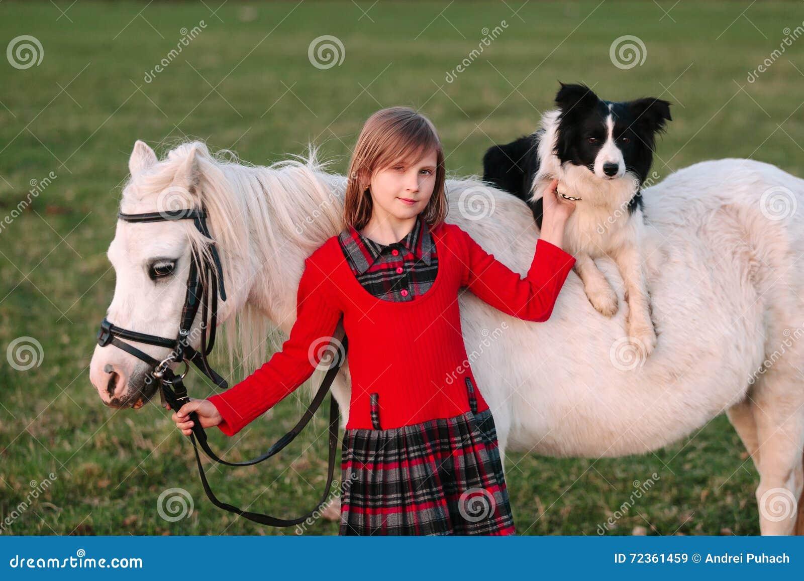 女婴年轻人 红色礼服 在马背上狗 小的白马小马