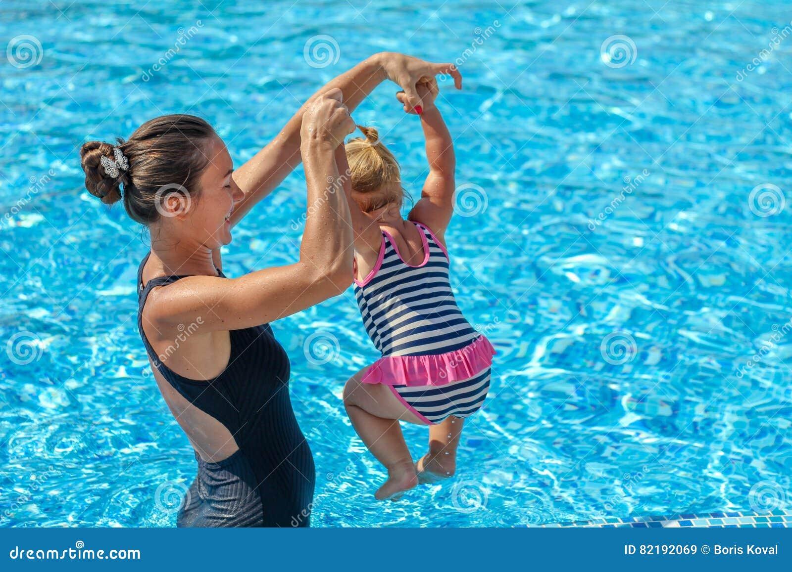 女婴在与她的母亲的水池学会游泳