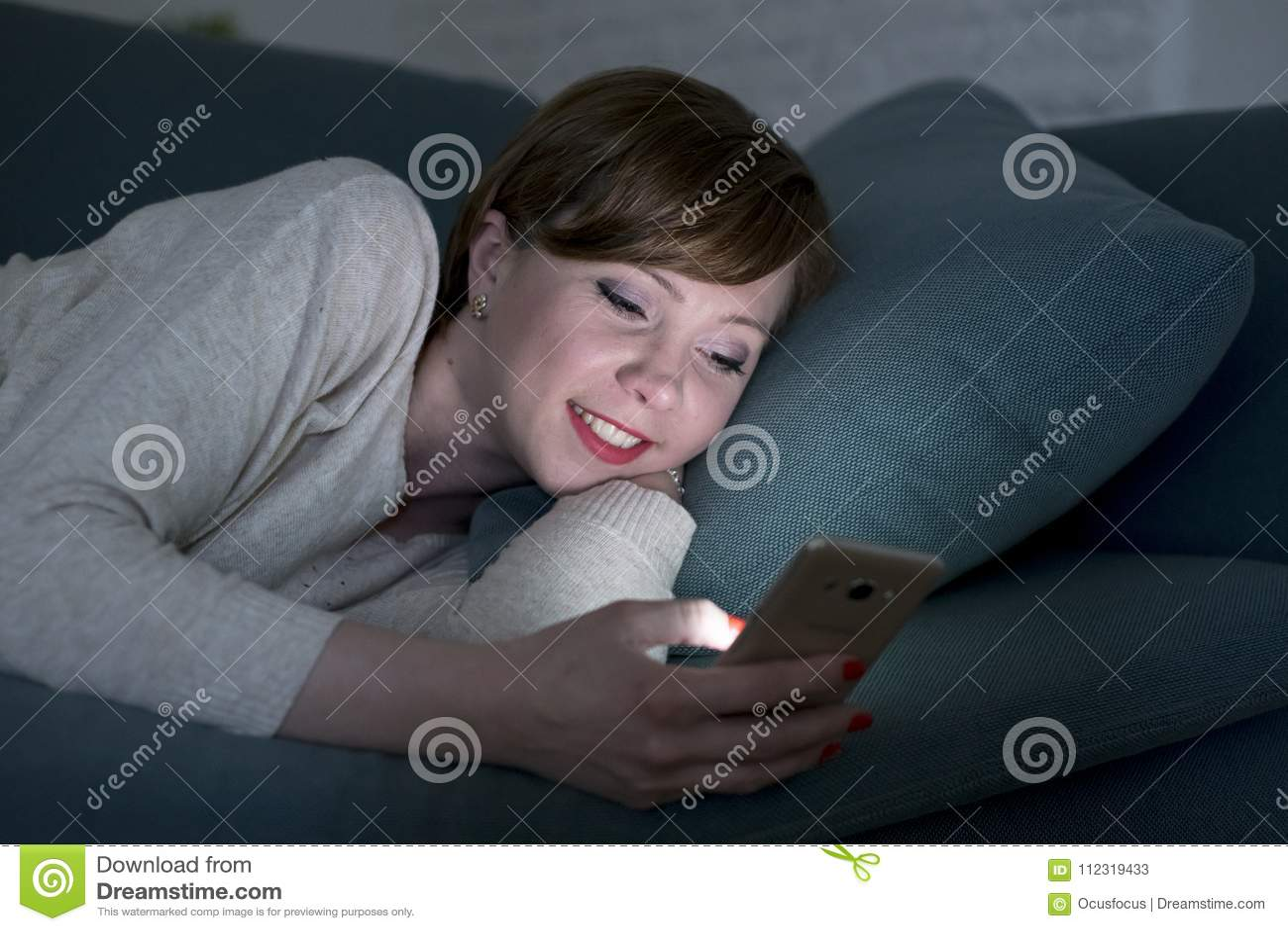 她的后说谎在家庭长沙发的20s的年轻俏丽和愉快的红色头发妇女或30s或床使用手机在夜微笑的relaxe