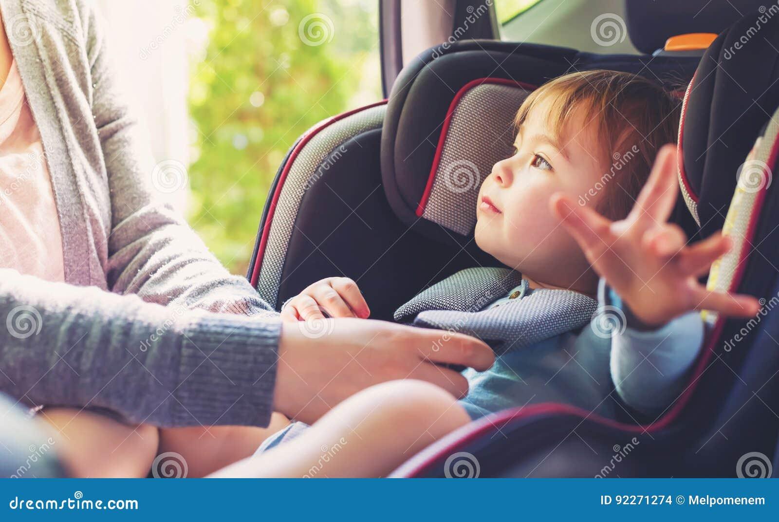 她的汽车座位的小孩女孩