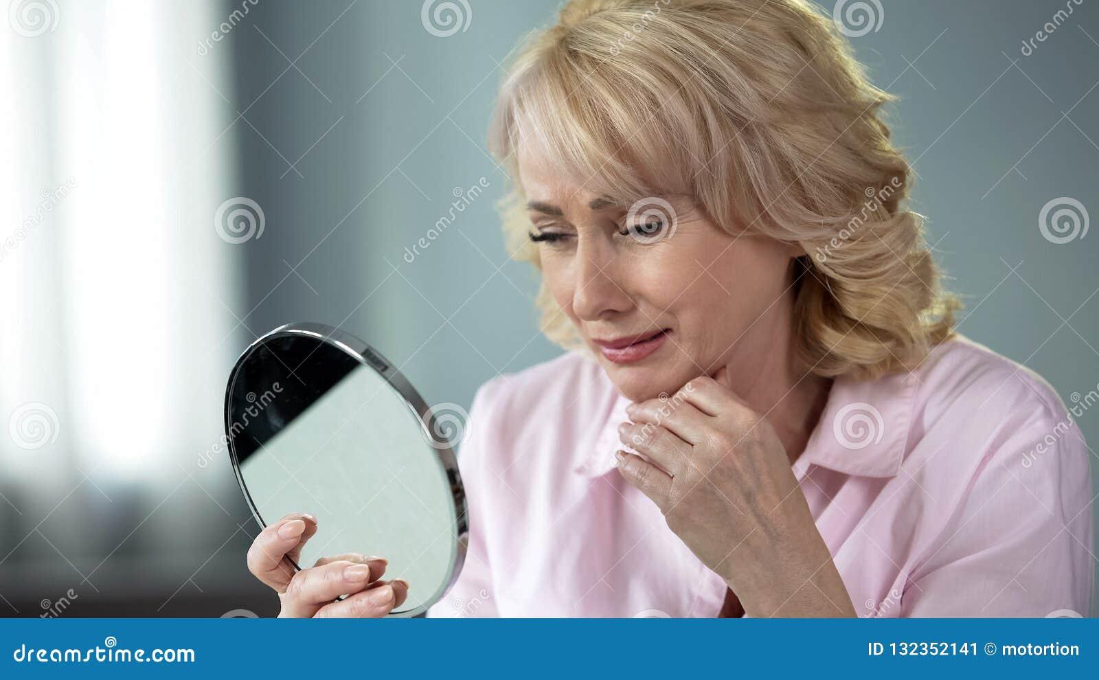 她50的夫人看在镜子记住年轻和健康皮肤,乡情的