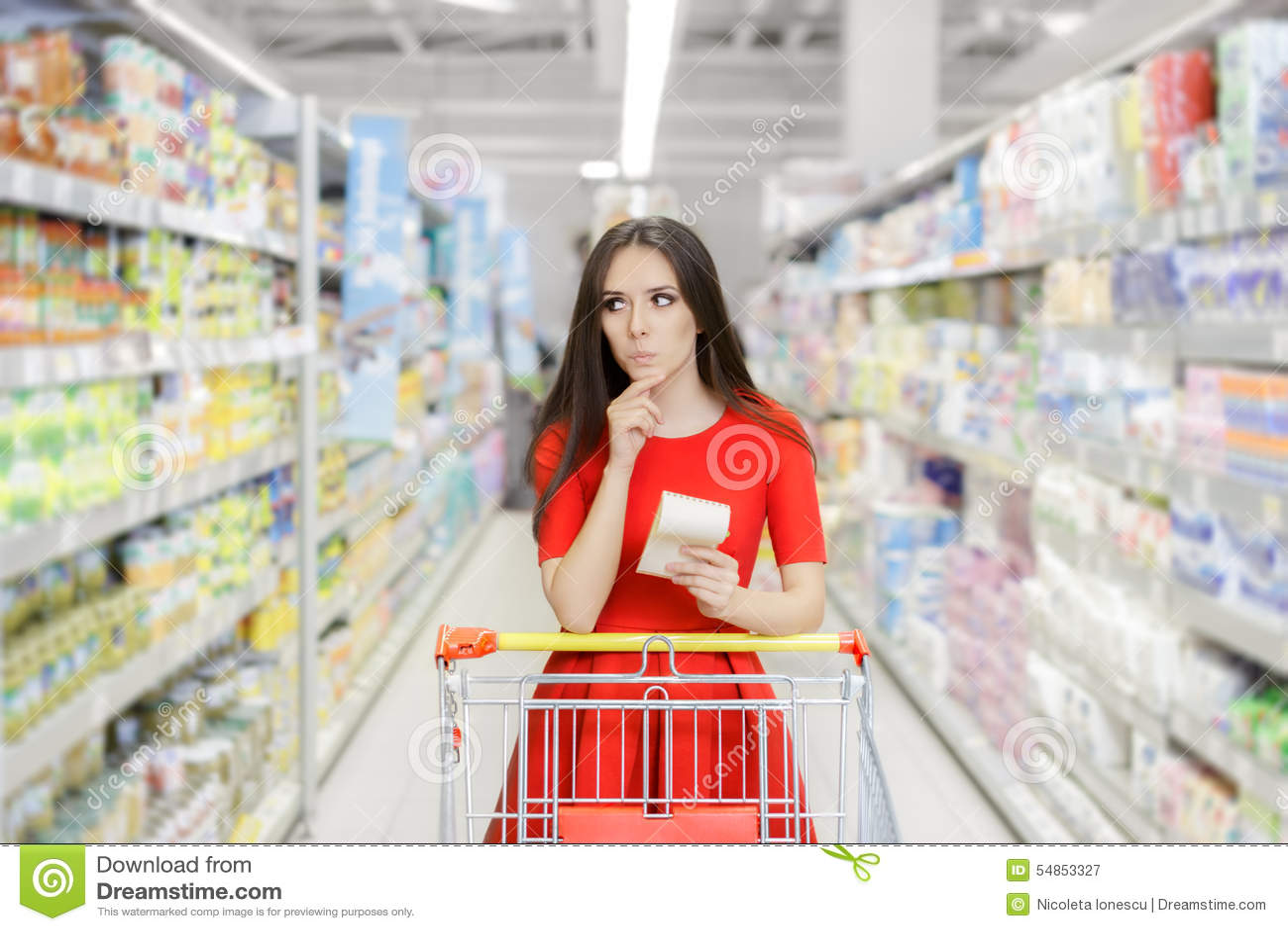 好奇妇女在有购物单的超级市场