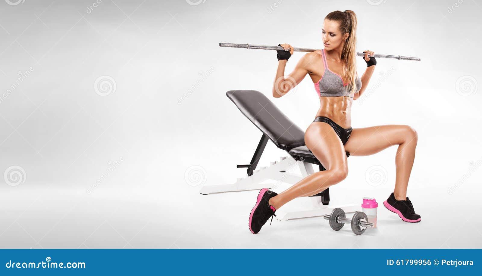 好性感的妇女坐一种长凳和锻炼与哑铃