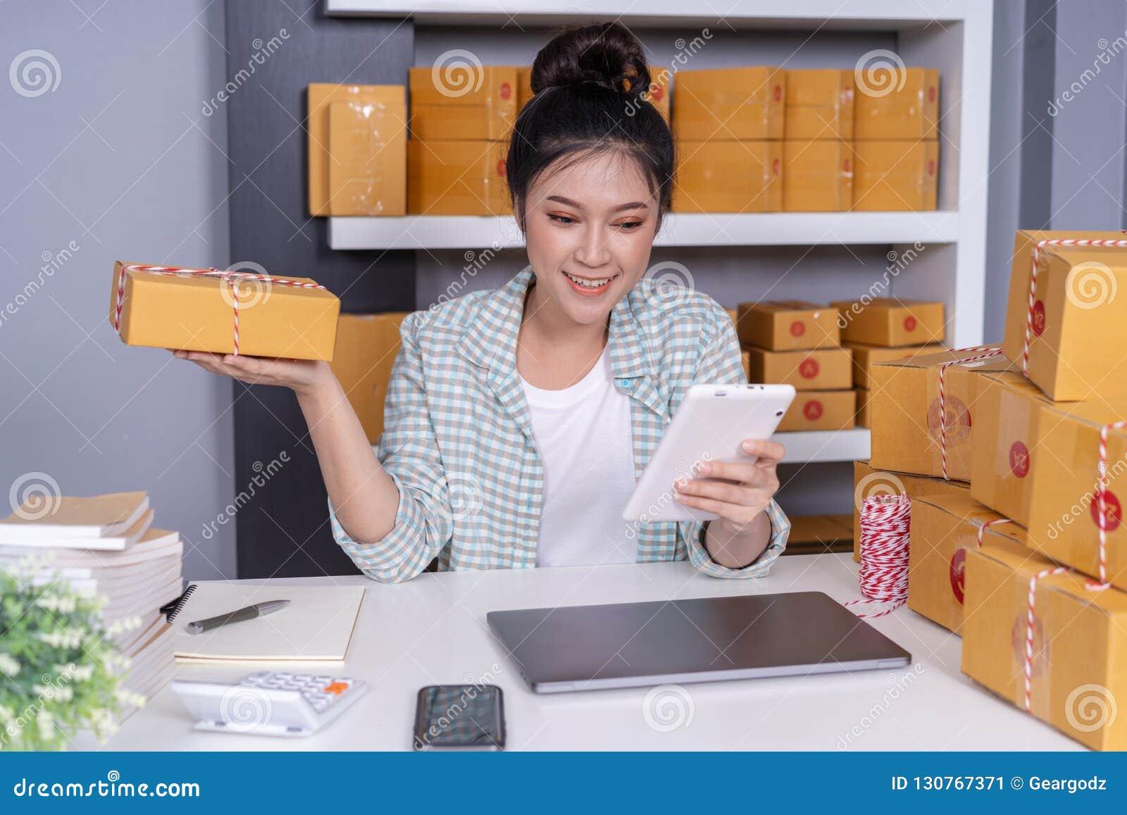 妇女与她的数字片剂和传讯者小包箱子一起使用在