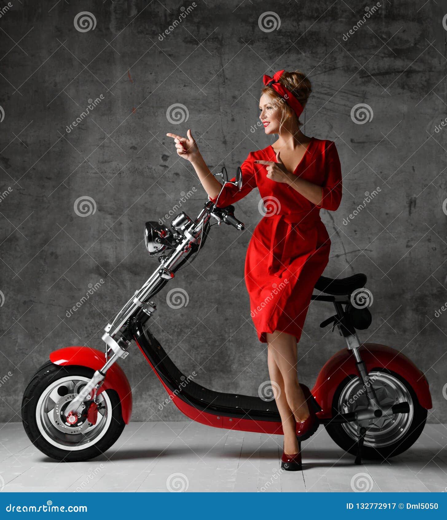 妇女乘驾坐指向手指的摩托车自行车滑行车画报减速火箭的样式笑微笑的红色礼服