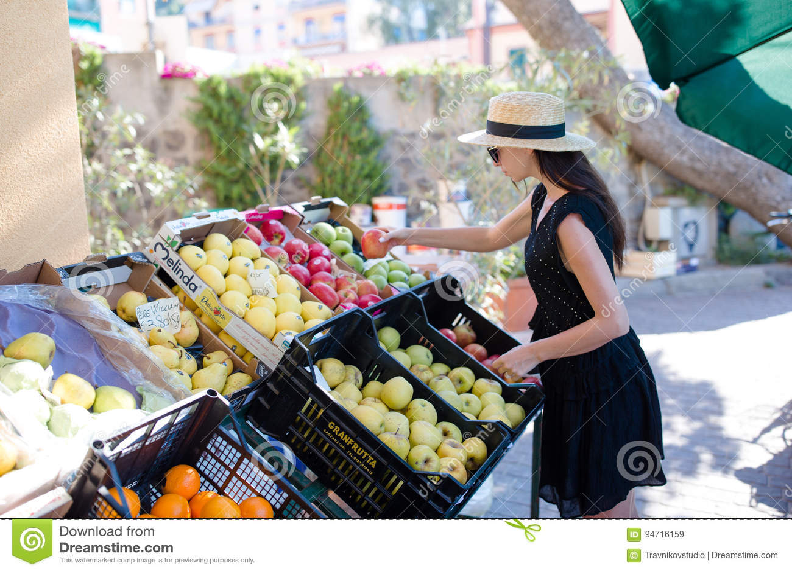 妇女买的水果和蔬菜在农夫室外市场上 少妇购物画象健康生活方式的