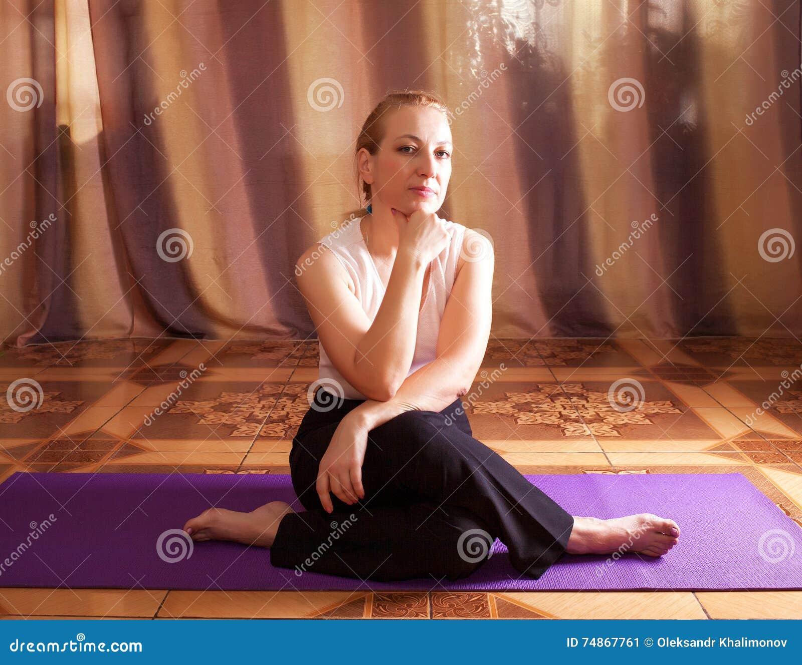 妇女信奉瑜伽者坐地板