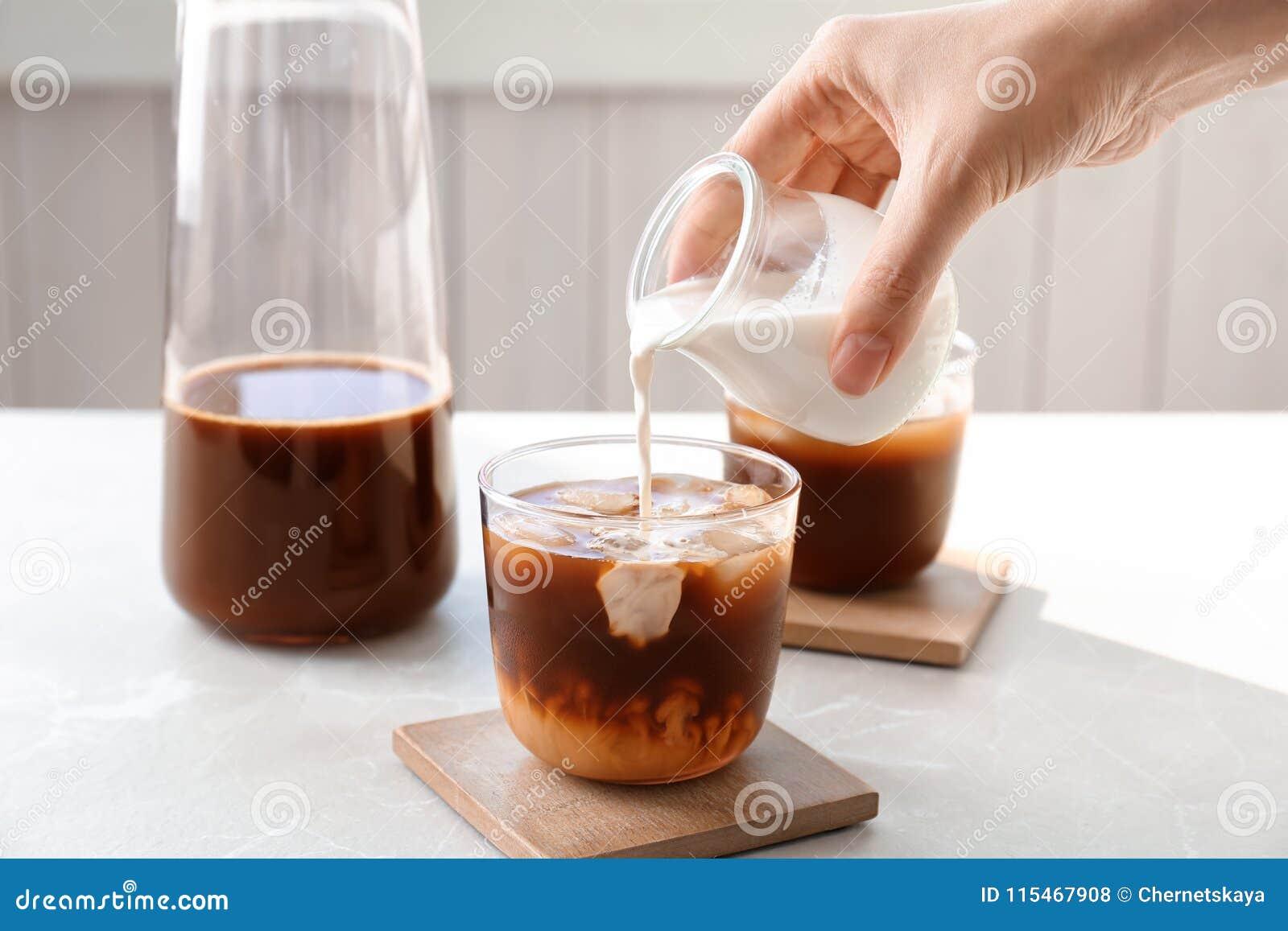 妇女倾吐的牛奶到玻璃里用冷的酿造咖啡