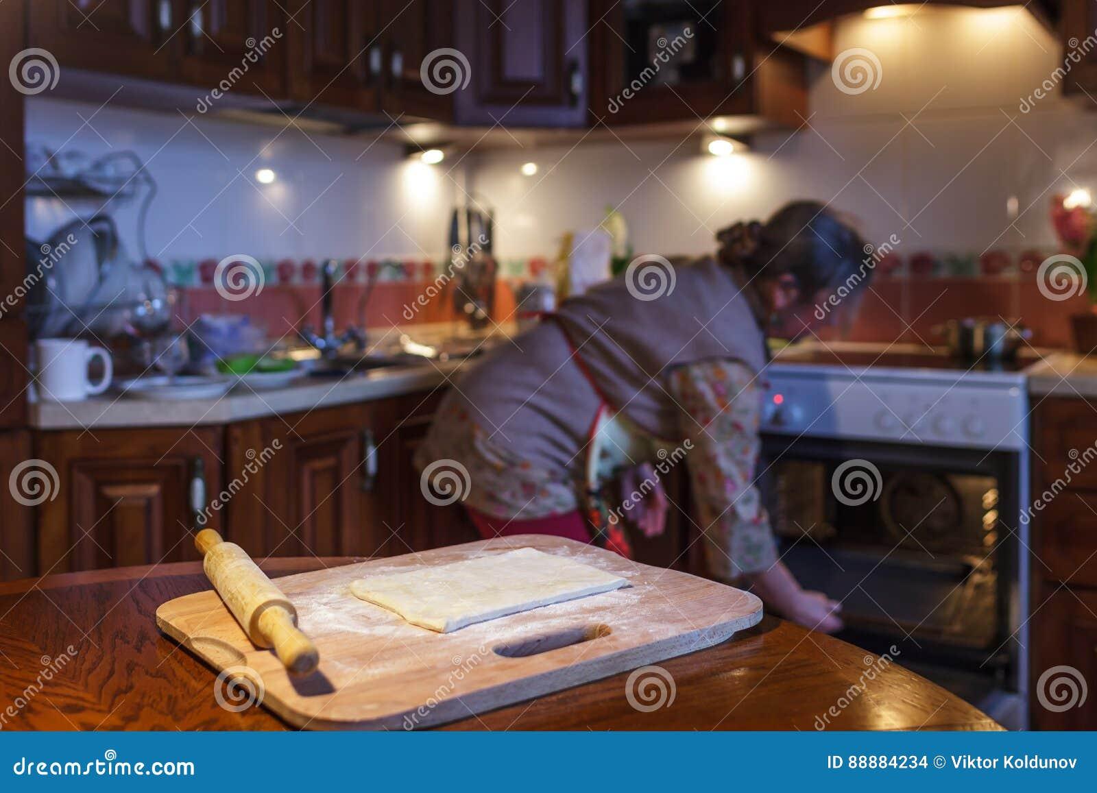 妇女准备饼,给烤箱加热