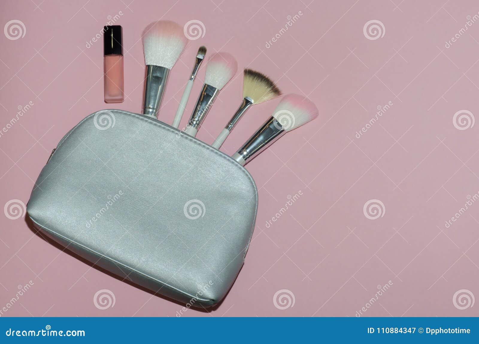 妇女化妆袋子,在桃红色背景组成美容品 构成刷子和桃红色唇膏 顶视图, flatlay 装饰co