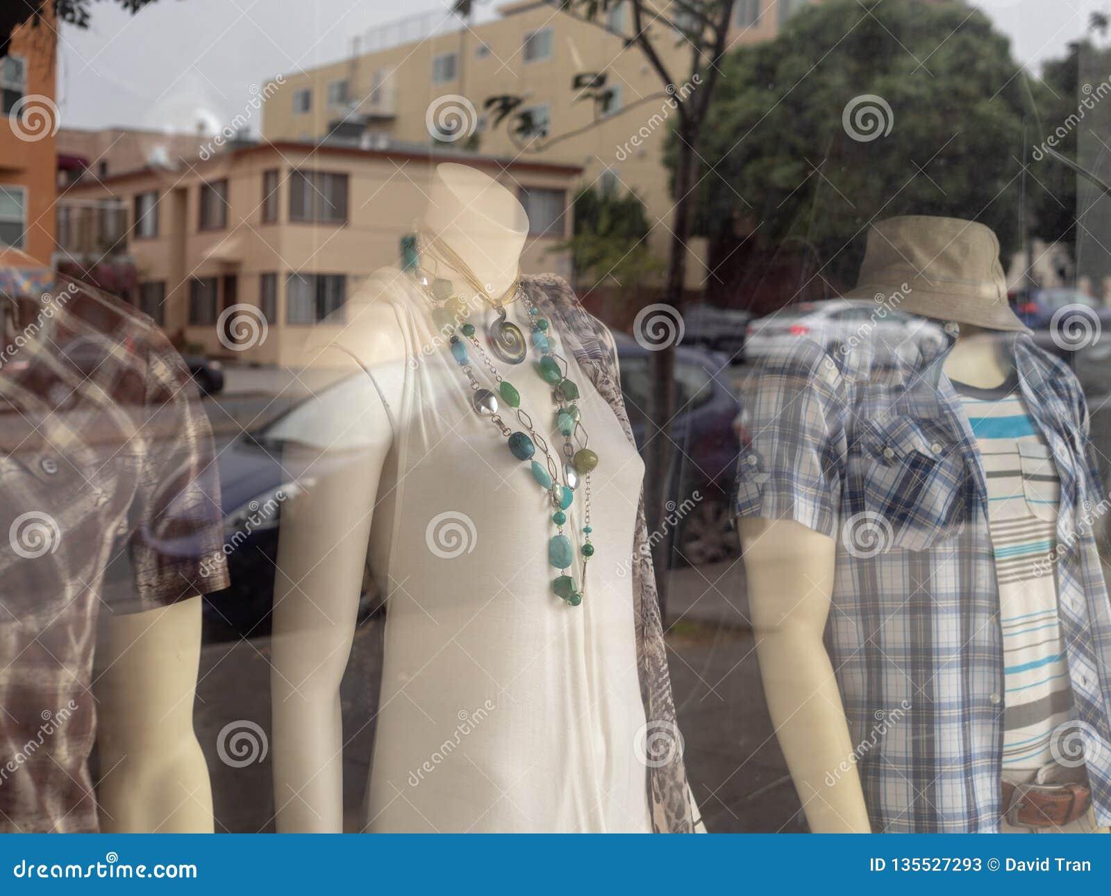妇女和人站立在店面窗口里的时装模特形象