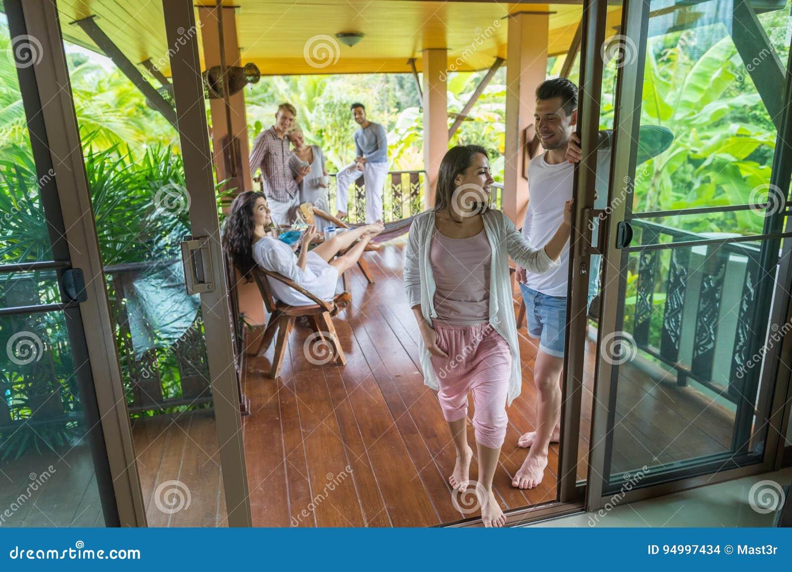 妇女和人从与谈话人的小组,朋友户外愉快微笑的夏天大阳台去