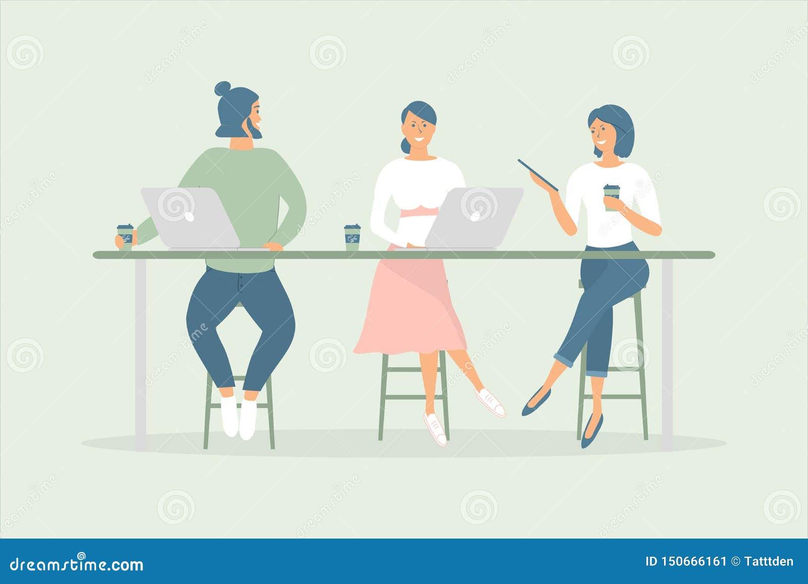 妇女和坐在现代办公室或咖啡馆的书桌的人朋友或者同事,工作在笔记本和片剂,食用咖啡,谈话