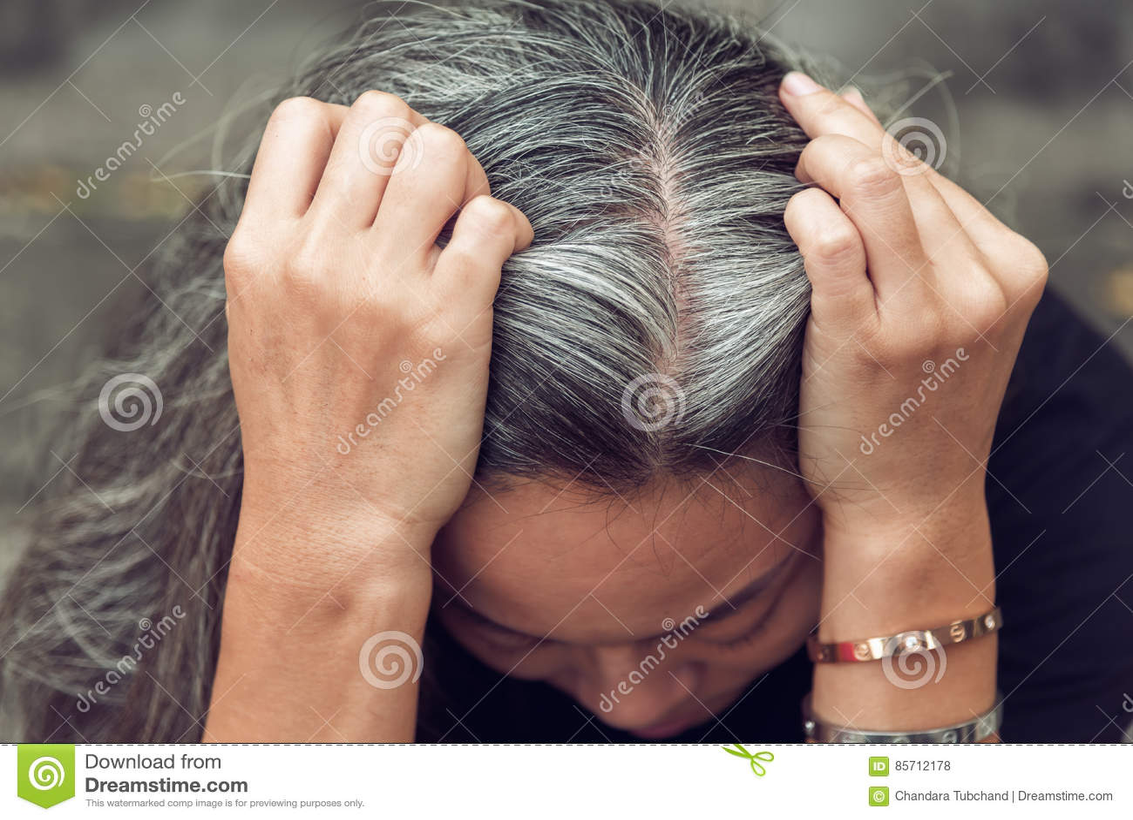 妇女和灰色头发有看担心的被注重的面孔的下来