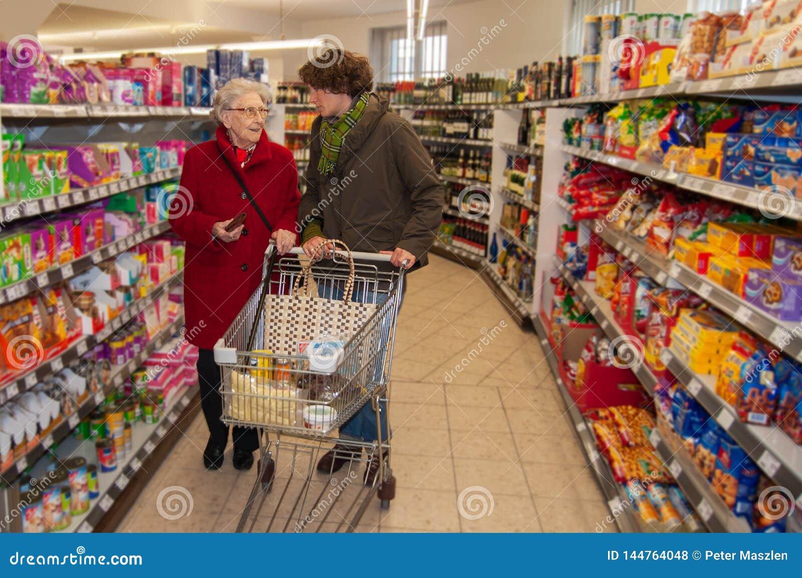 妇女和资深妇女向购物求助在超级市场