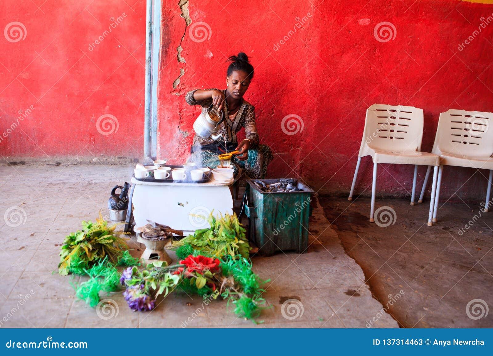 妇女咖啡为游人做准备用一个传统方式