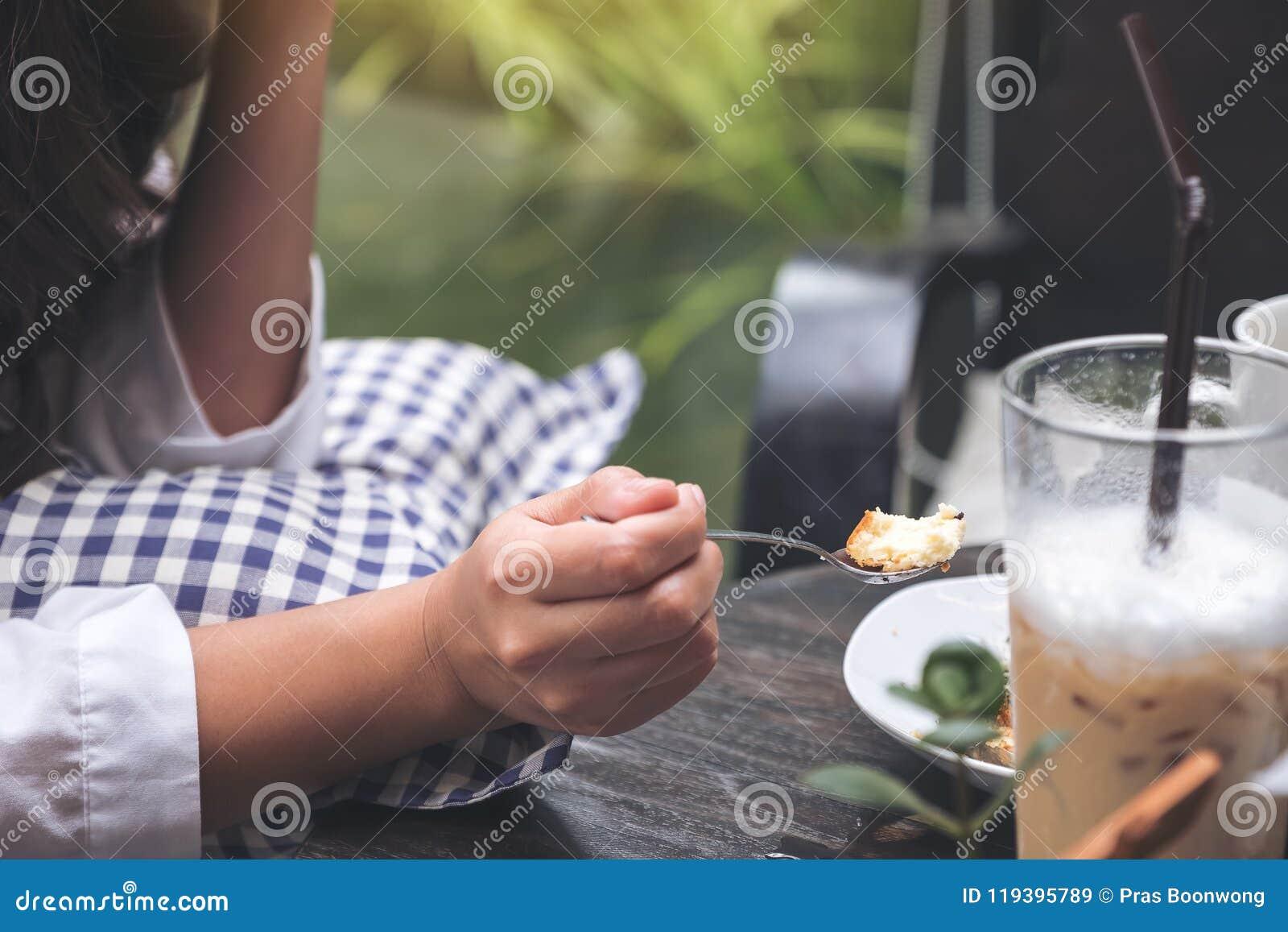 妇女喜欢吃乳酪蛋糕和咖啡在咖啡馆