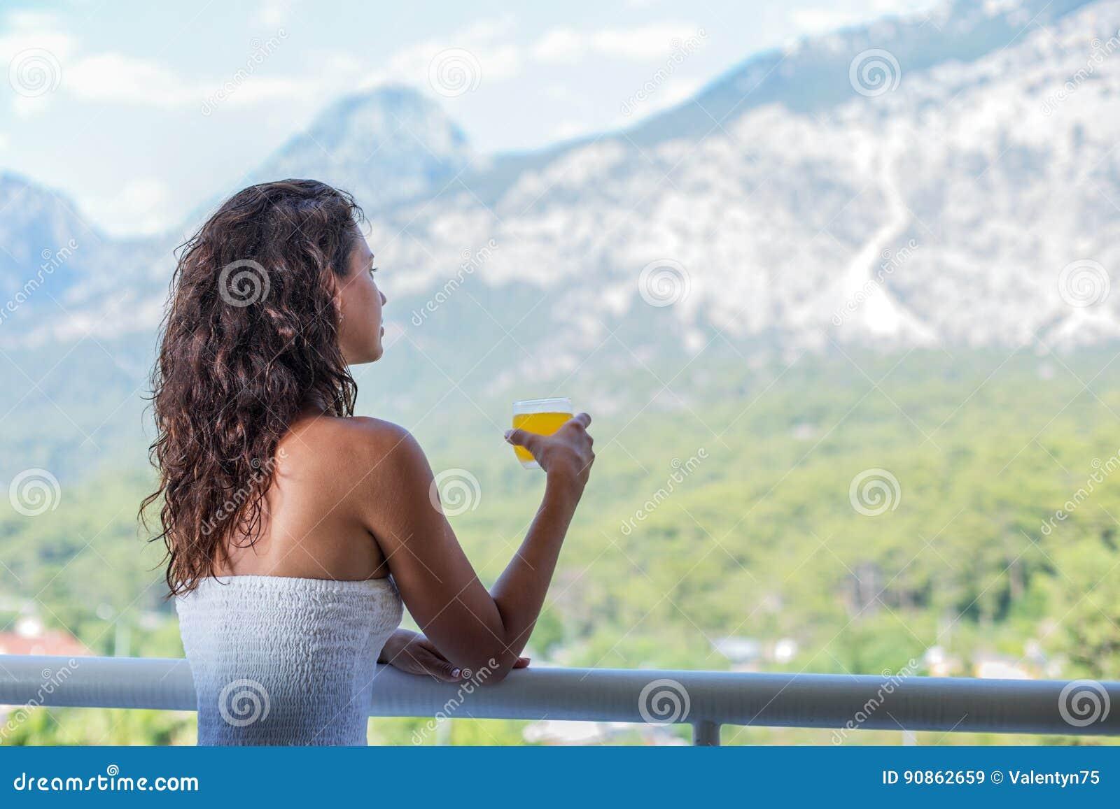 妇女喝在旅馆阳台的橙汁