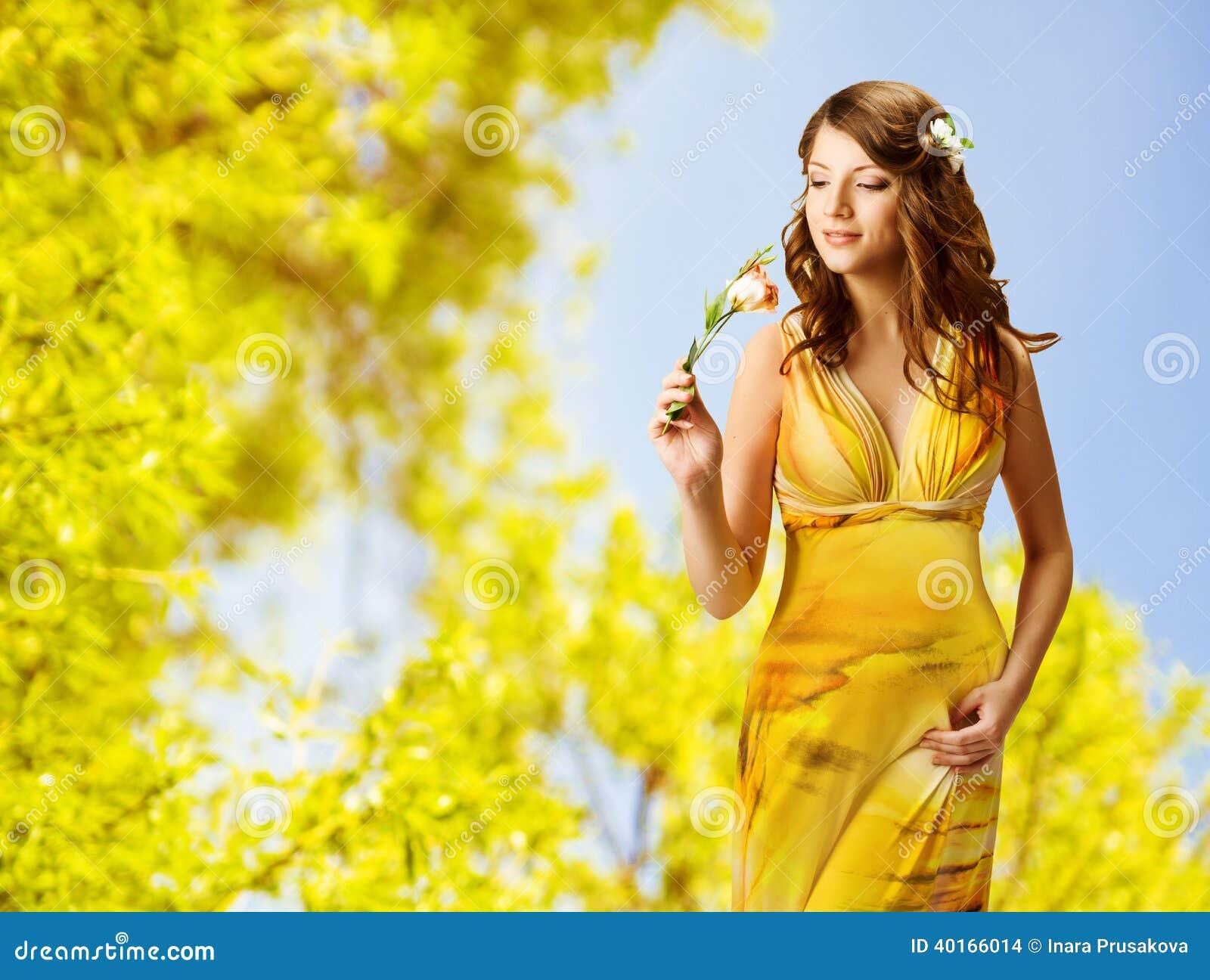 妇女嗅到的花,美丽的女孩的春天画象yel的
