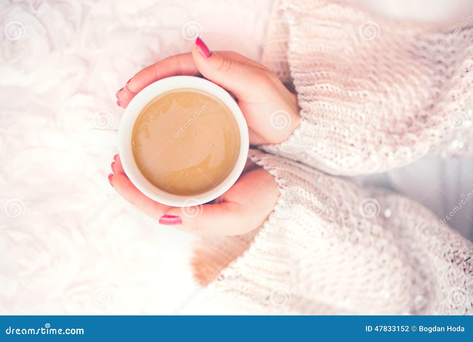 妇女在一个冬天递拿着一个杯子热的咖啡,浓咖啡,冷的天