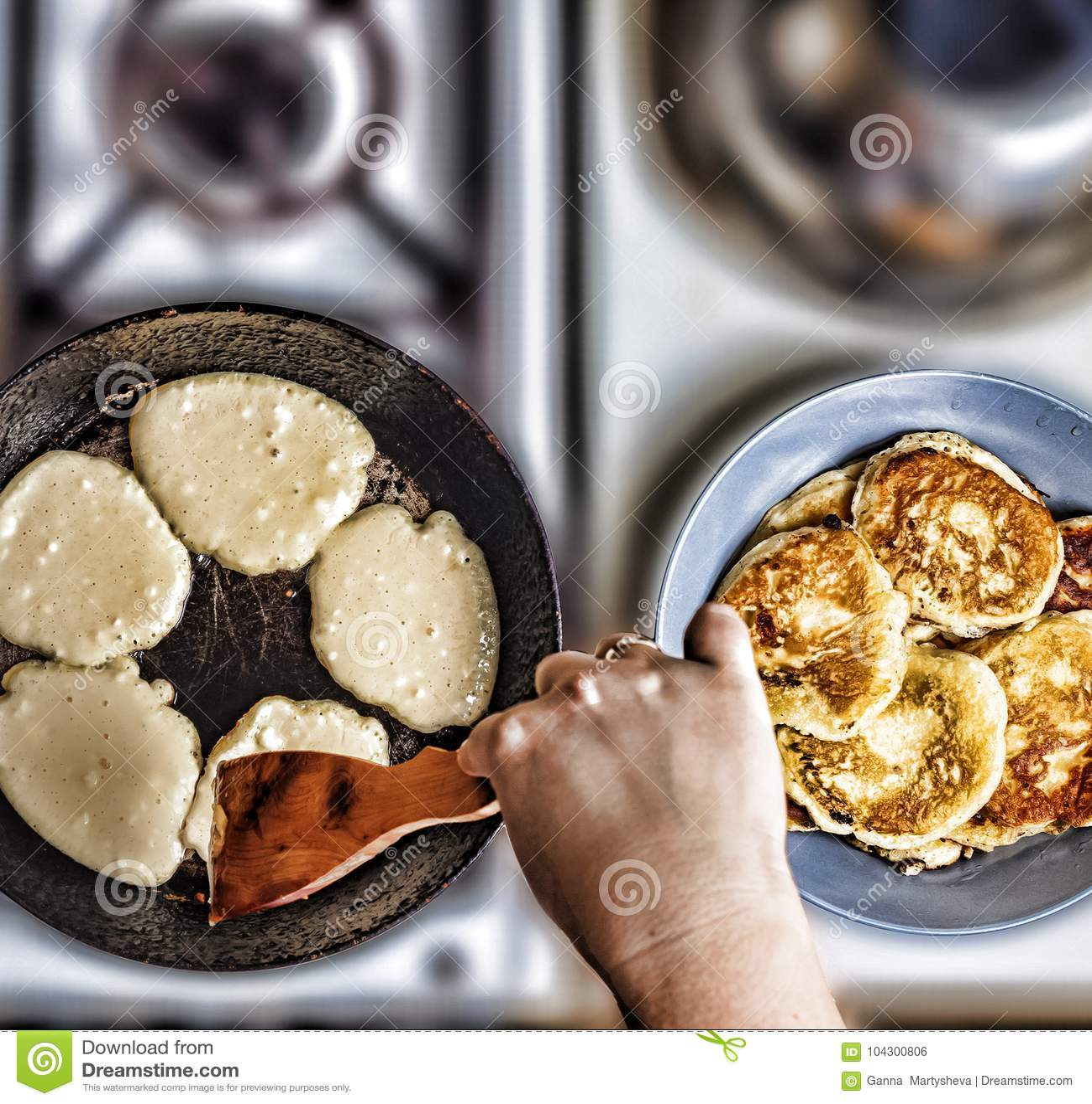 妇女在一个煎锅的油炸物薄煎饼在老煤气炉 概念:烹调,烘烤 在视图之上