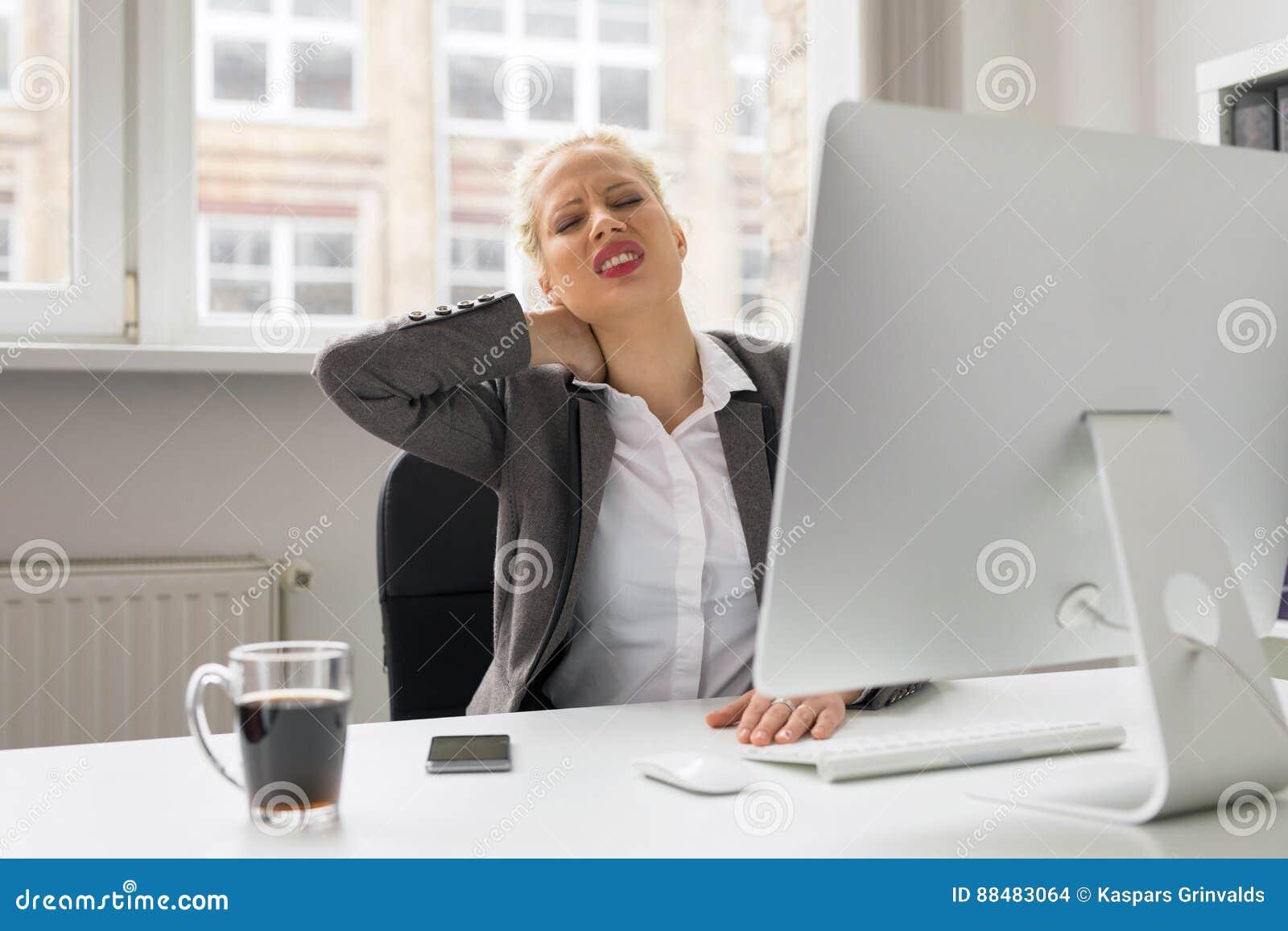 妇女在办公室在痛苦中的握她的脖子