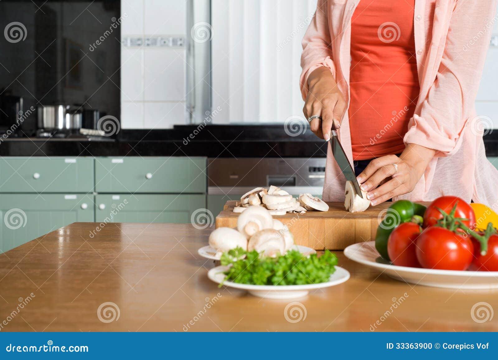 妇女在厨台的切口菜的中央部位