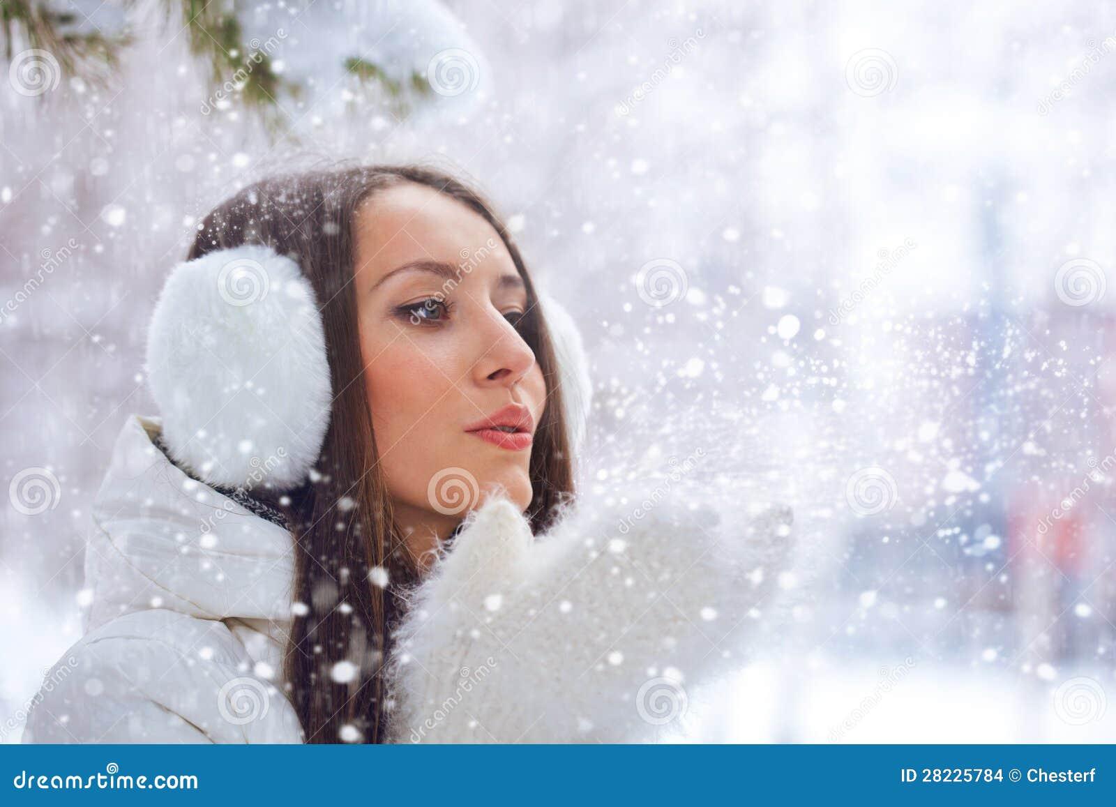 妇女在吹在雪的冬天公园
